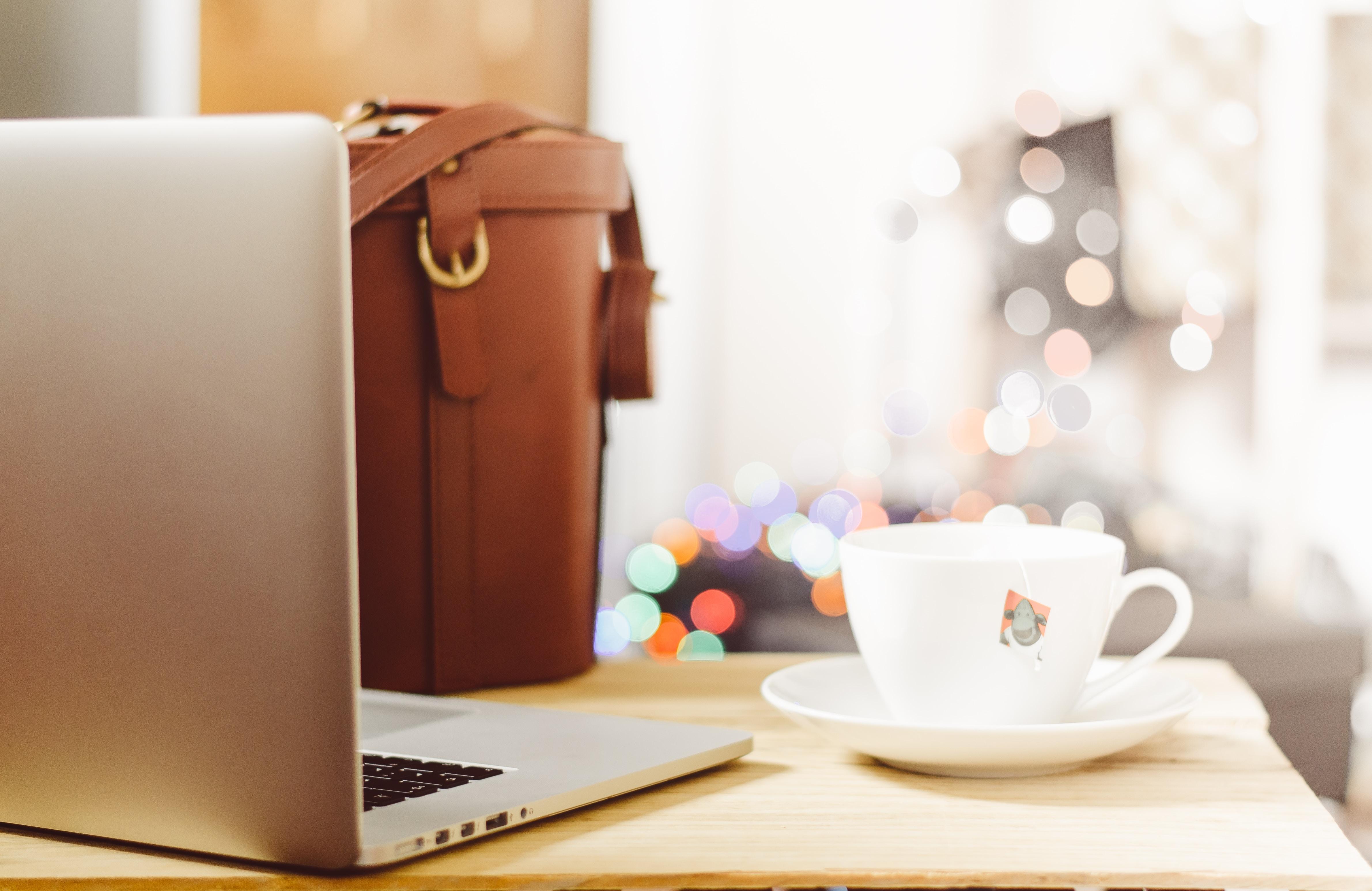 gray laptop beside teacup and bg
