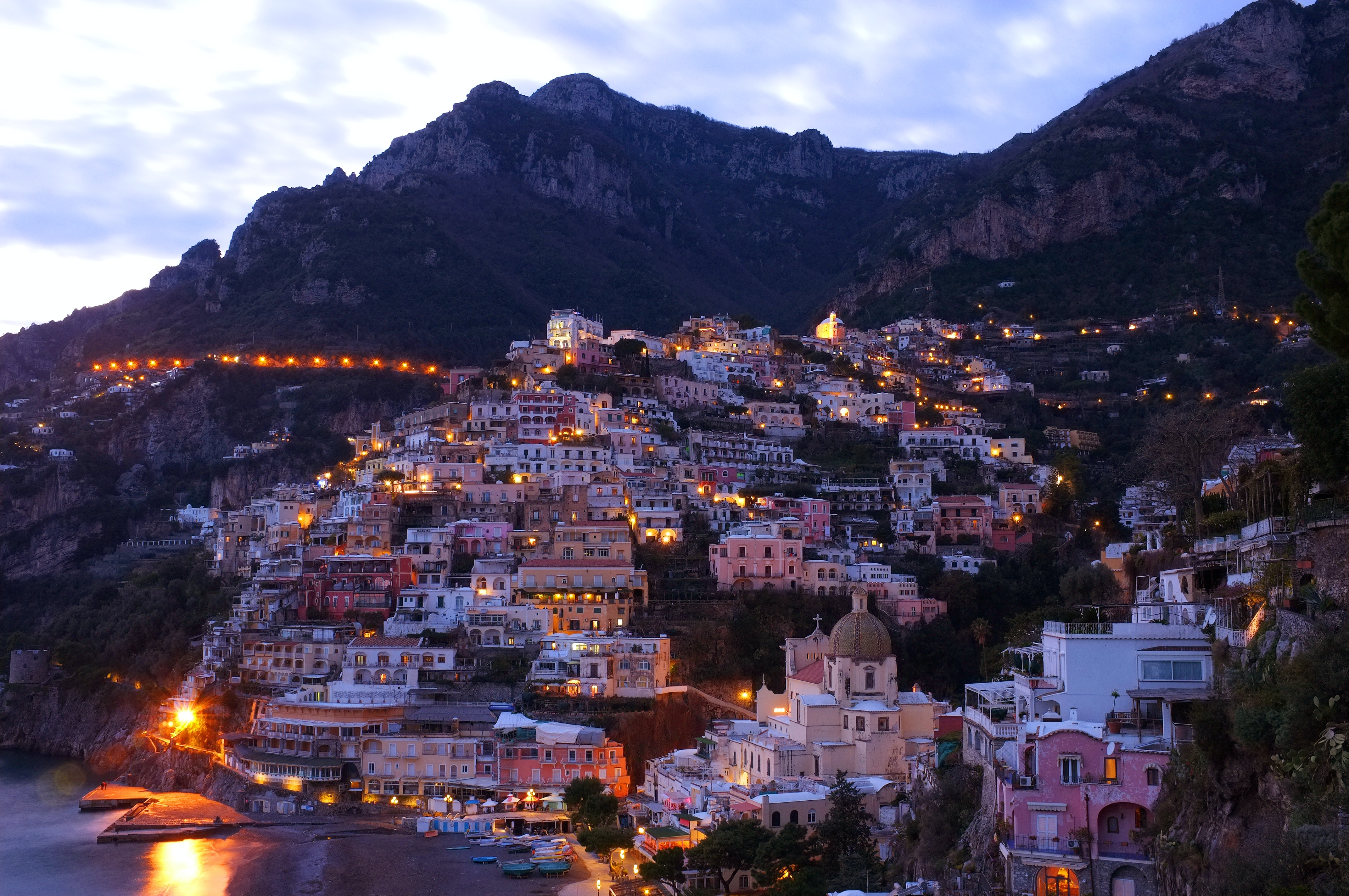 The small town of Positano on the side of a mountain in the evening