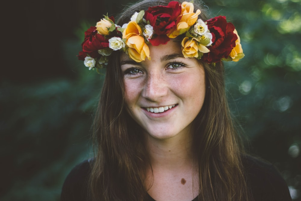 selective focus photography of smiling woman wearing floral headdress