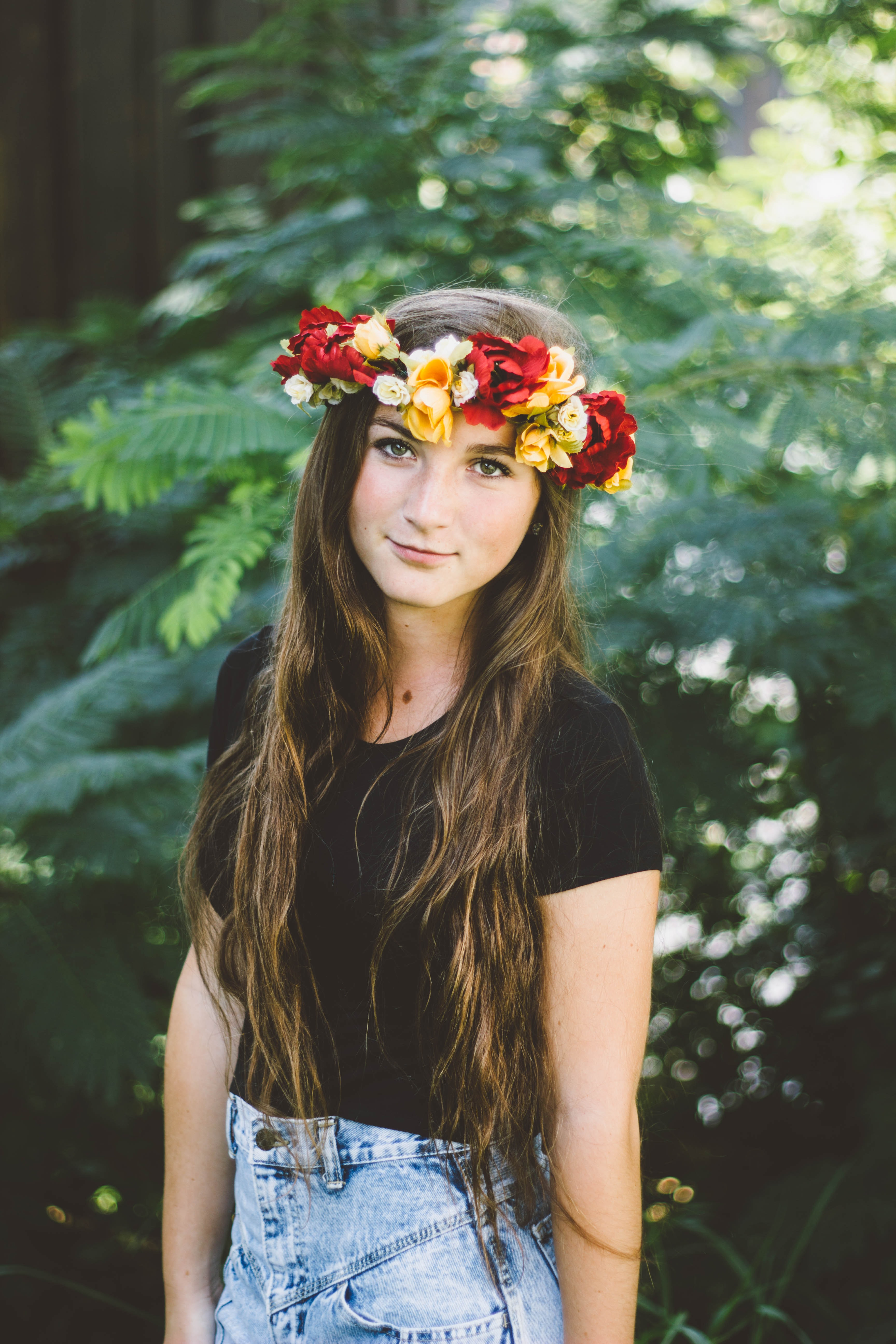 A young woman in a headband of red and yellow flowers