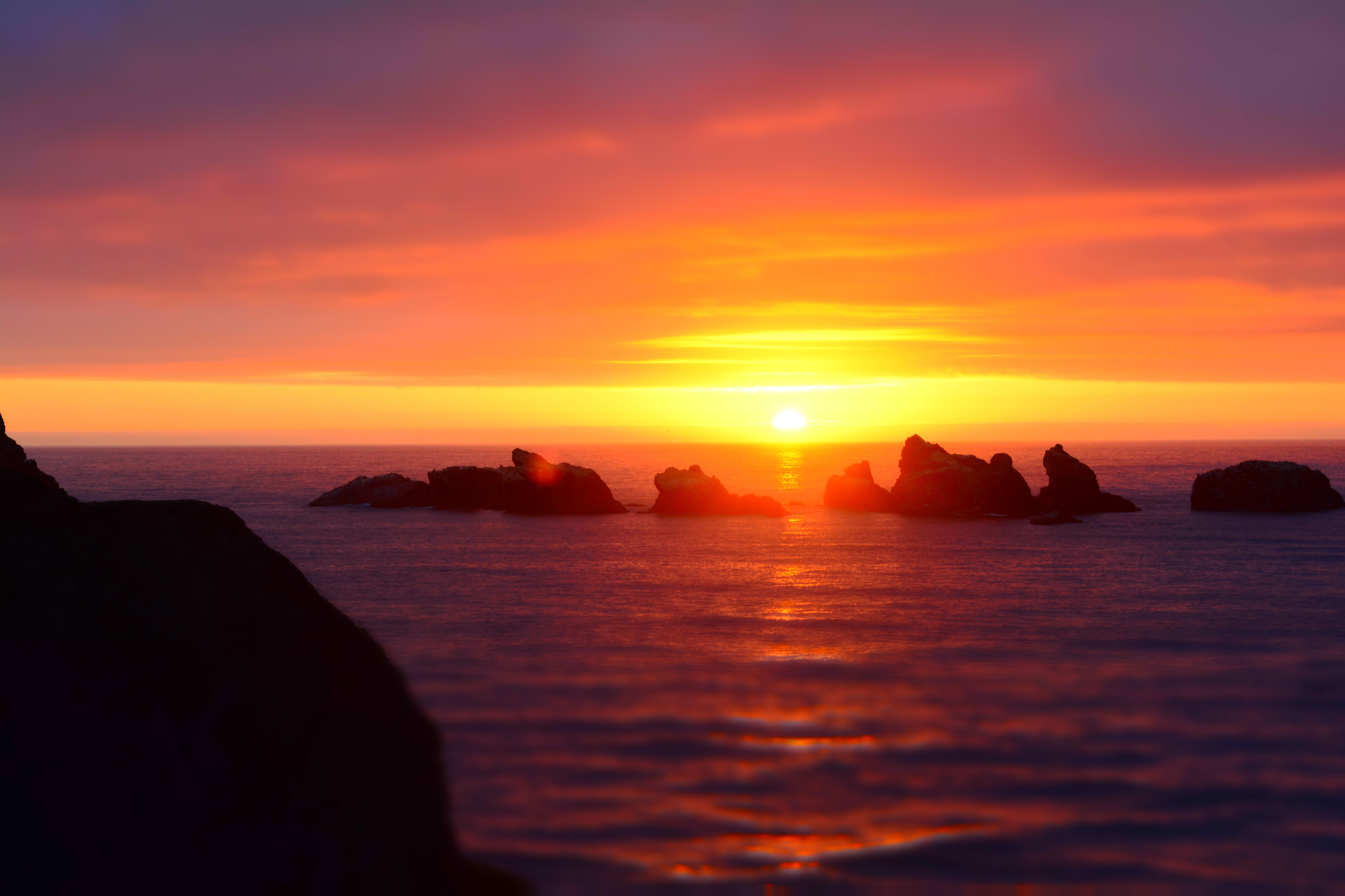 The sun setting on the horizon of the ocean at Bandon, with silhouetted rocks in the foreground, Good Morning Wednesday Quotes