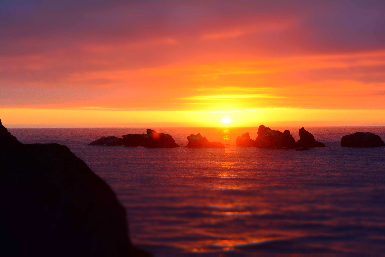 rocks on sea under sunset