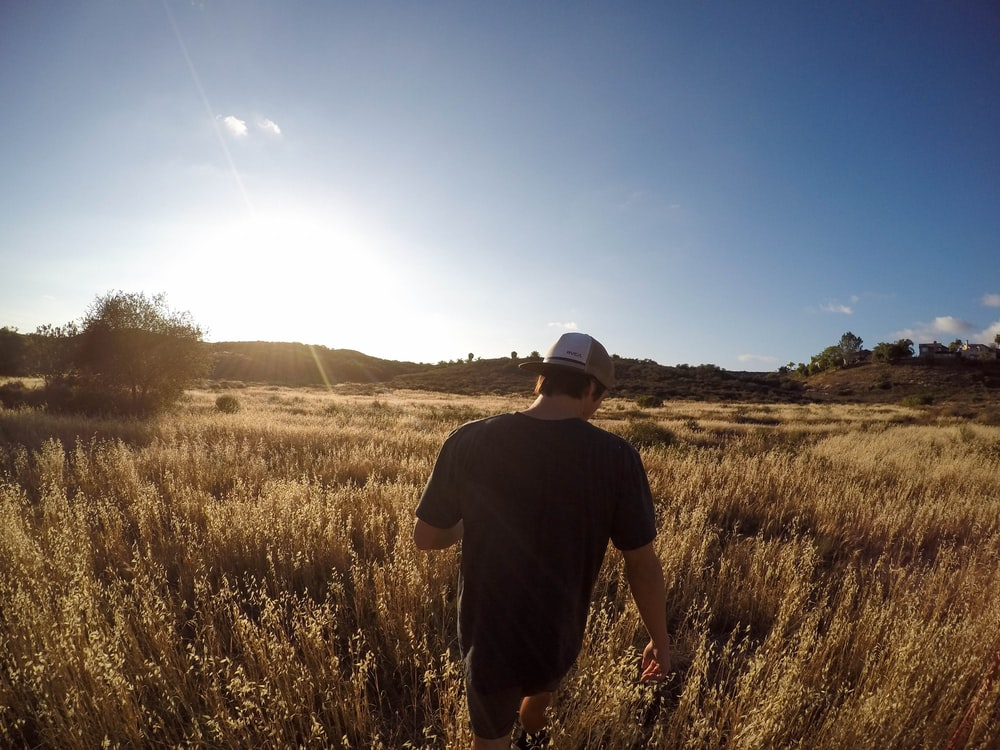 A man walking through a country field.
