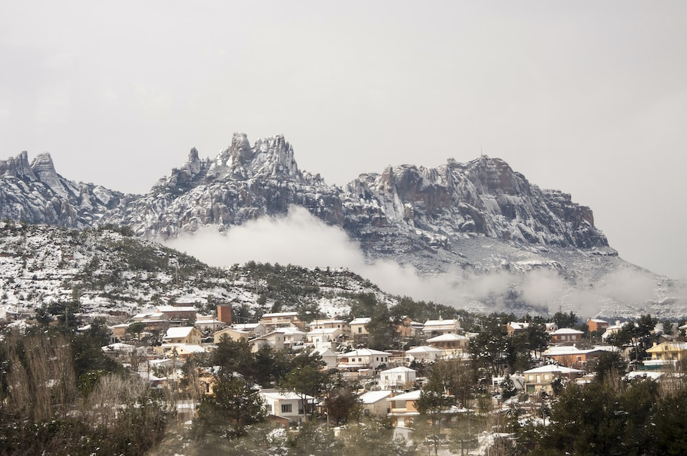 houses near mountain under white clouds