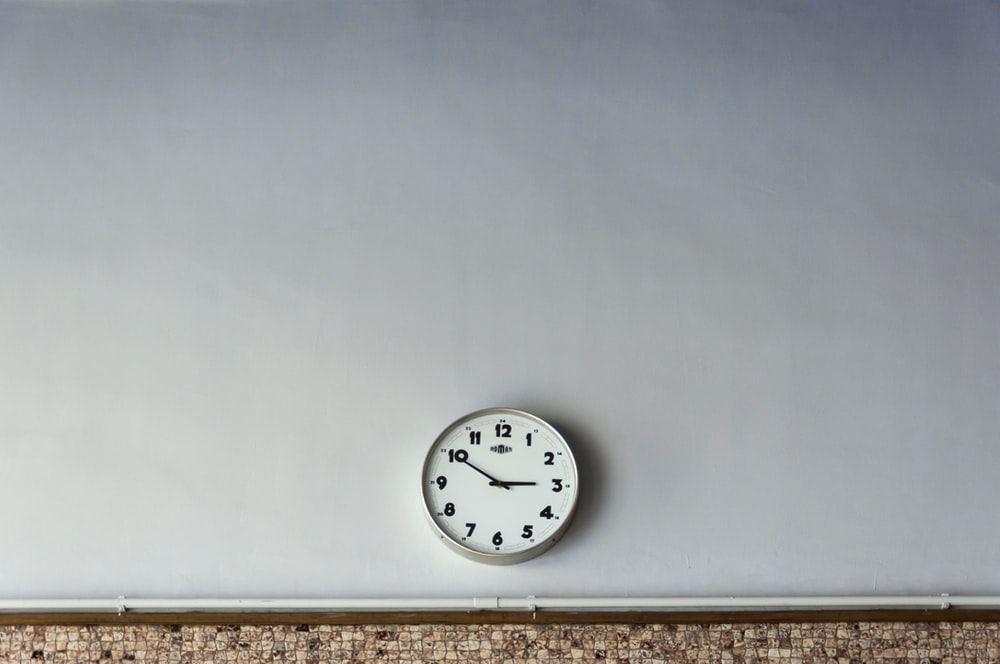 round white wall clock reading at 2:50