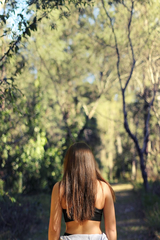woman wearing black sports bra facing the woods