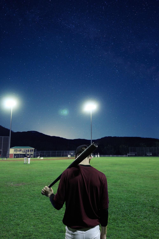 man holding baseball bat on green field