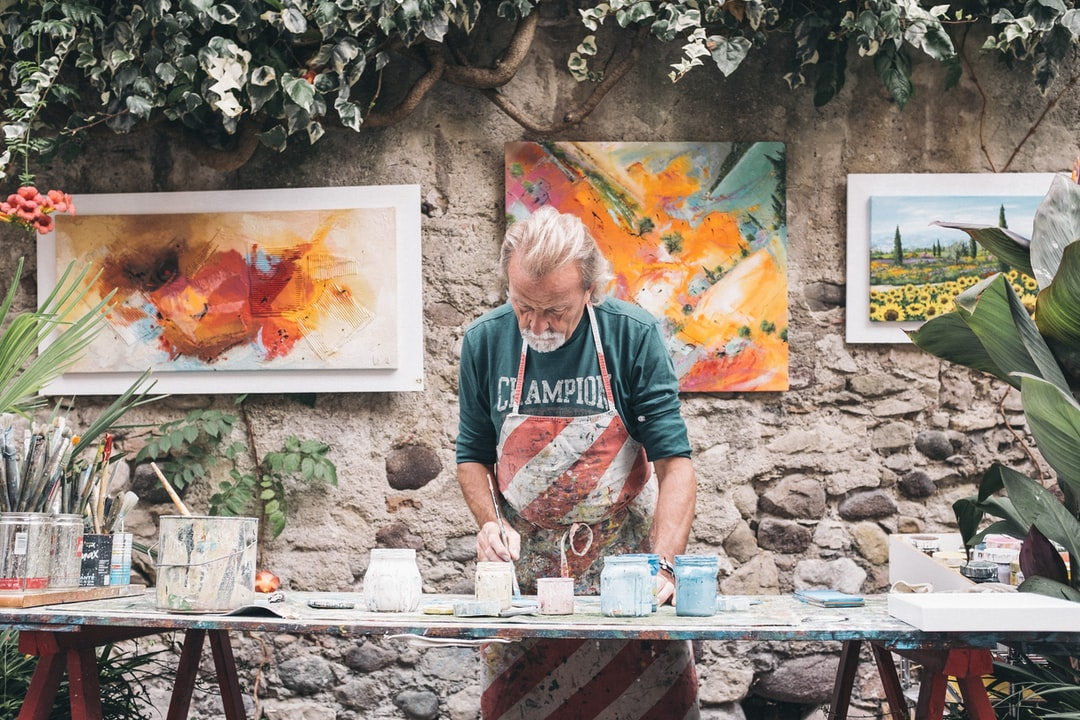 Man in striped apron paints canvases in Bardolino