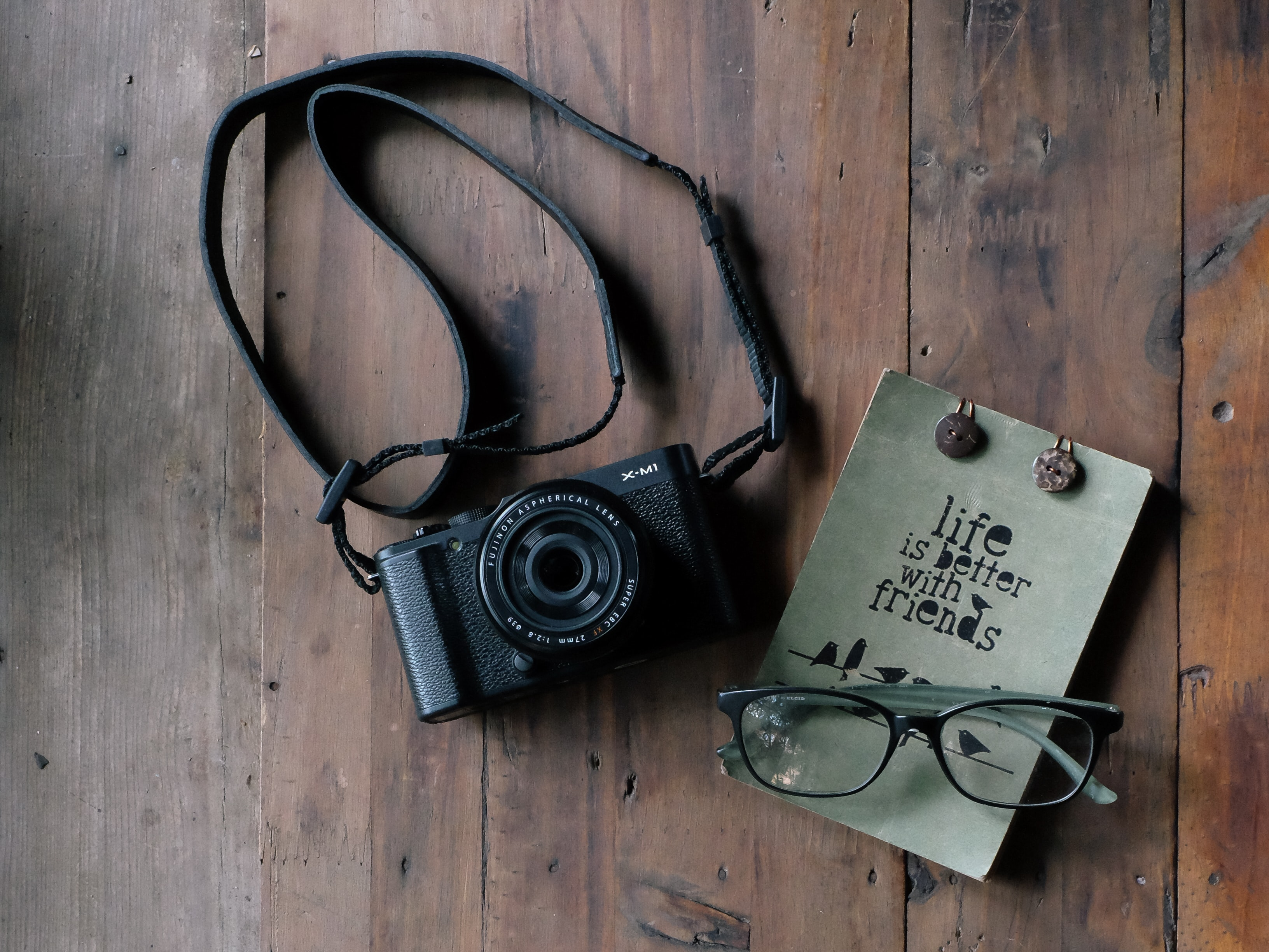 flat lay photography of black MILC camera and eyeglasses on brown table