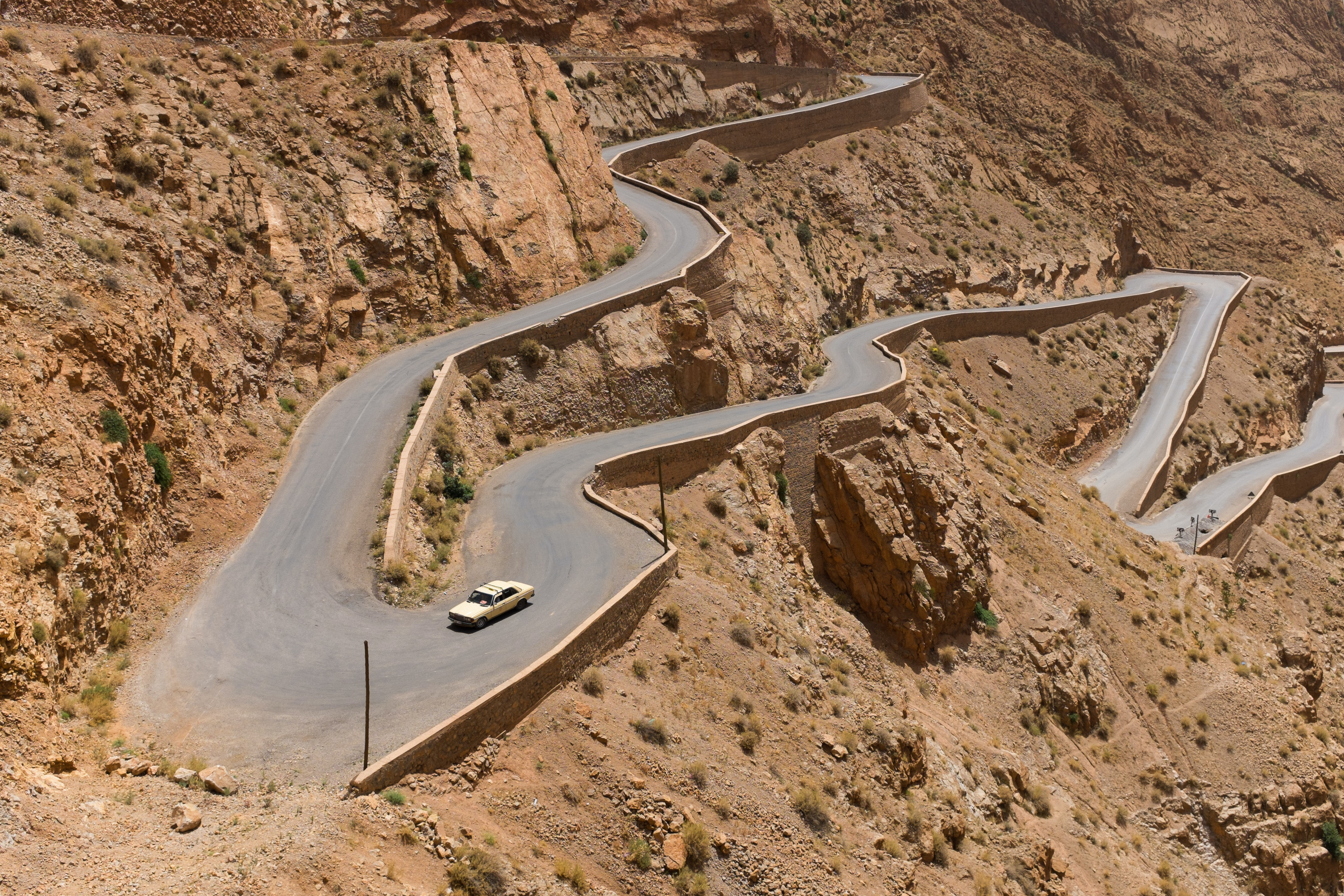 Long shot of winding mountain road in Morocco on sunny day