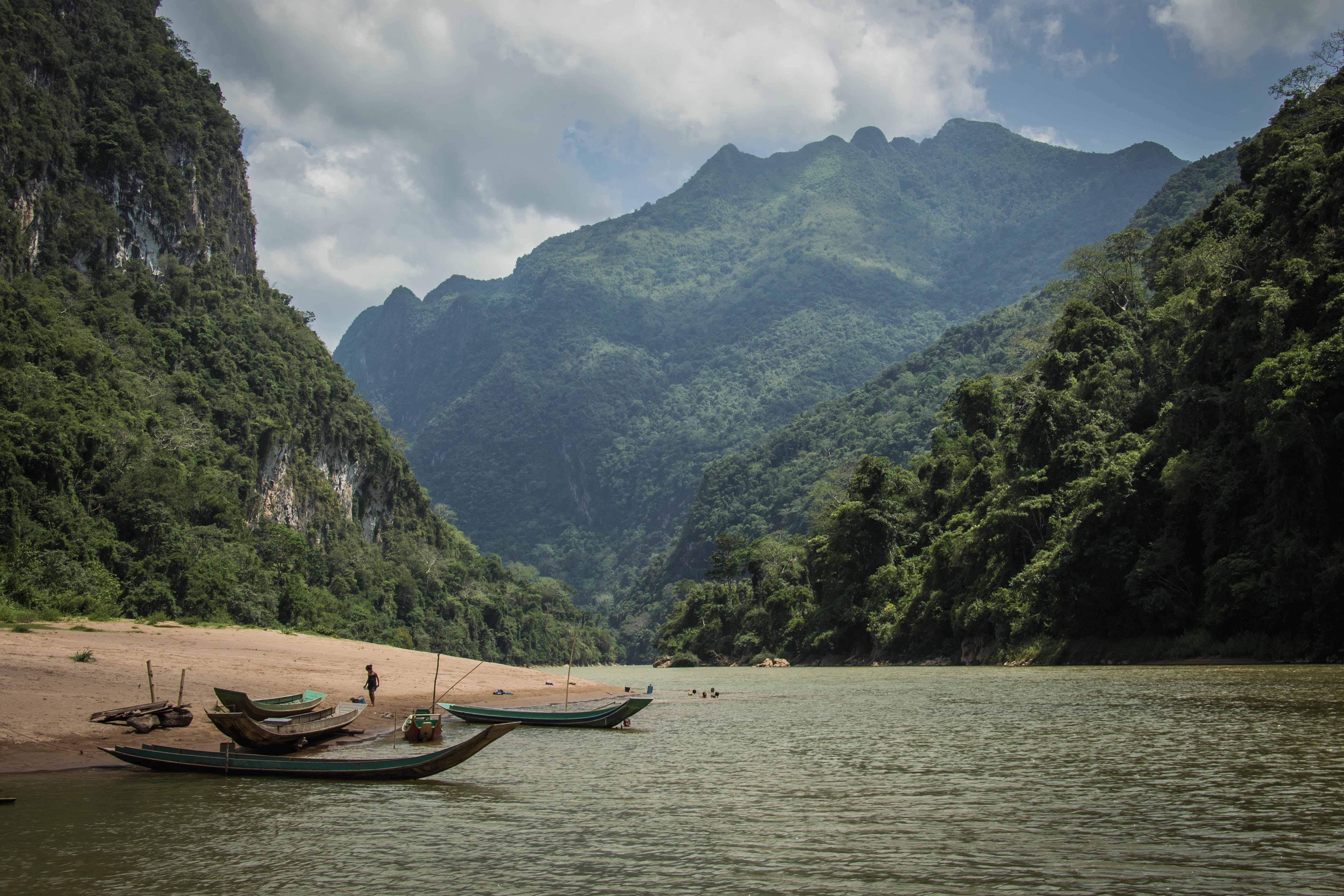 Canoes on a sandy river beach in the mountains in Laos