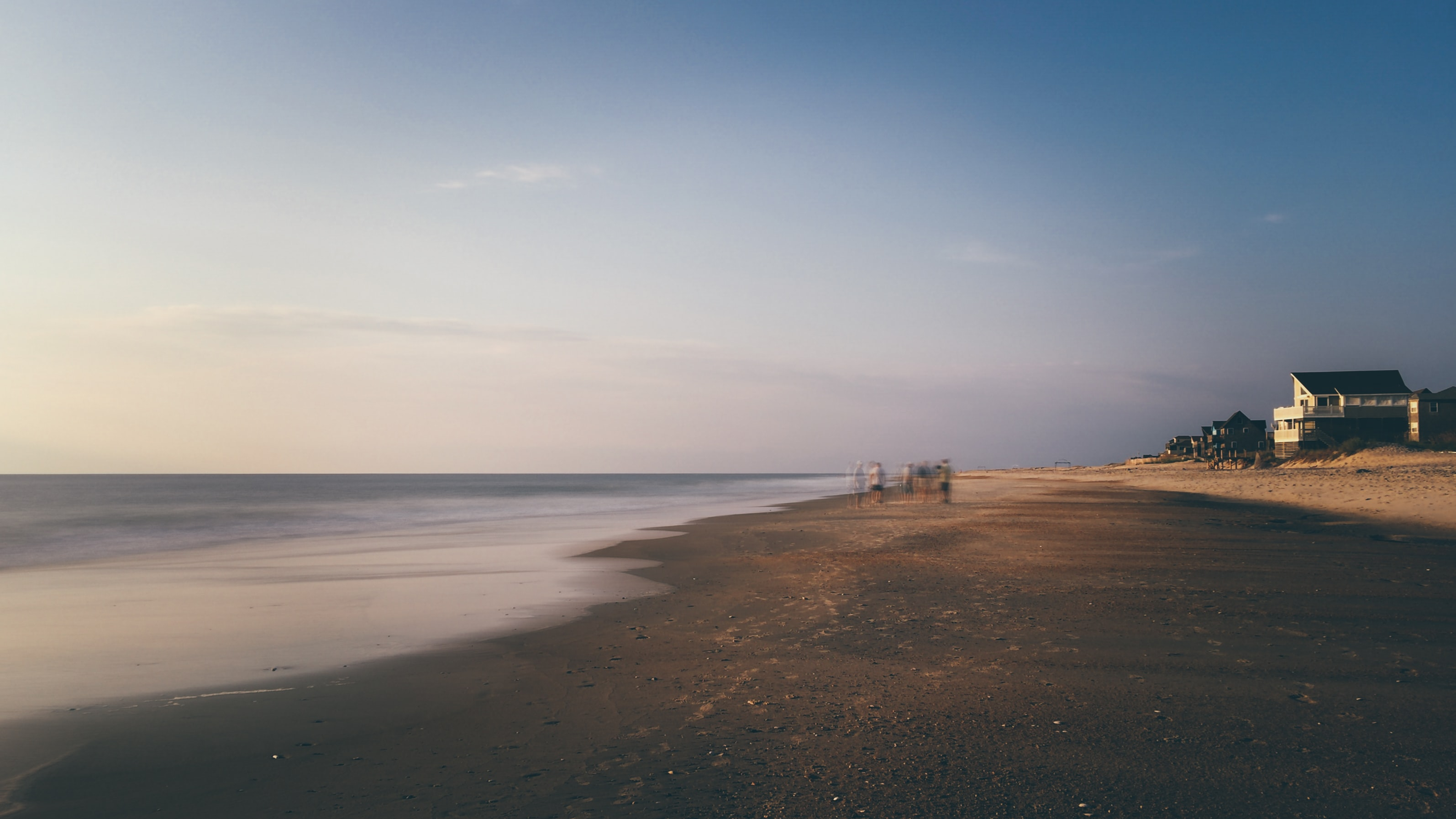 Blurry landscape capture of people doing early during sunrise at a beach in Rodanthe Pier