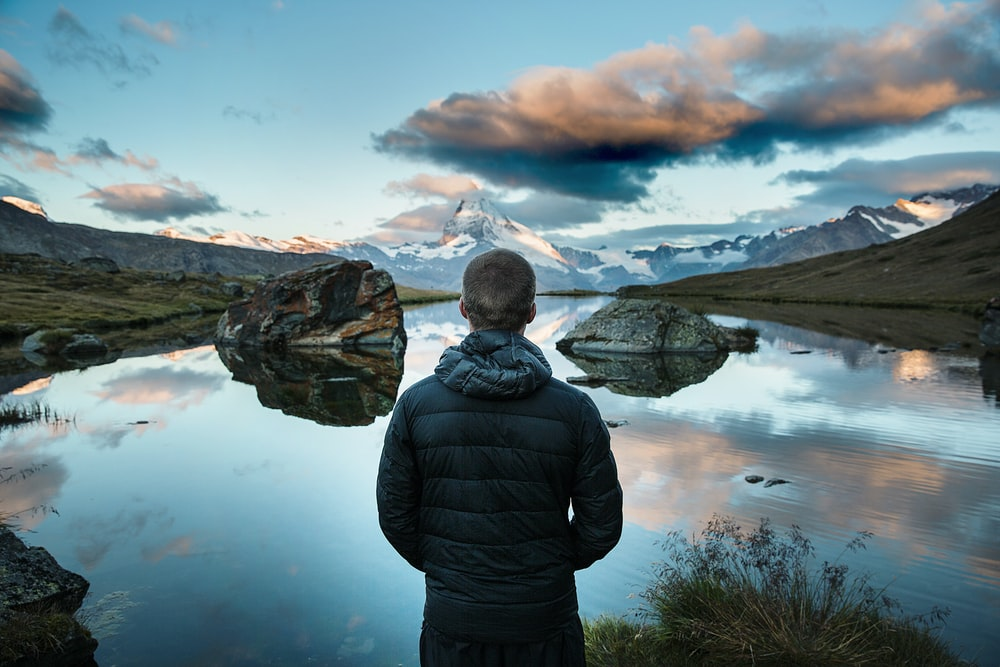 man standing in front view of lake surrounded with mountains