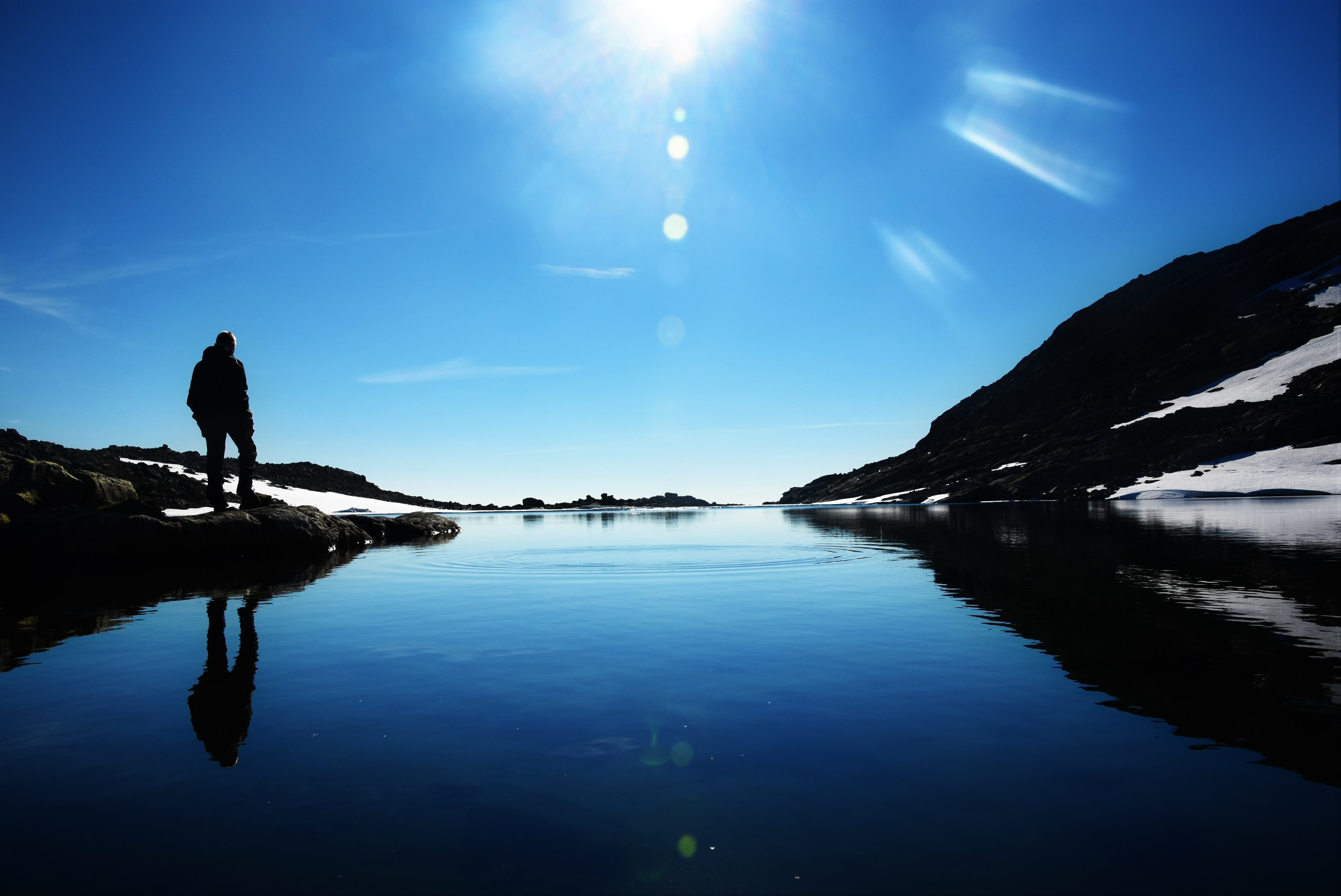 The silhouette of person at a lake looking at the sun and a mountain