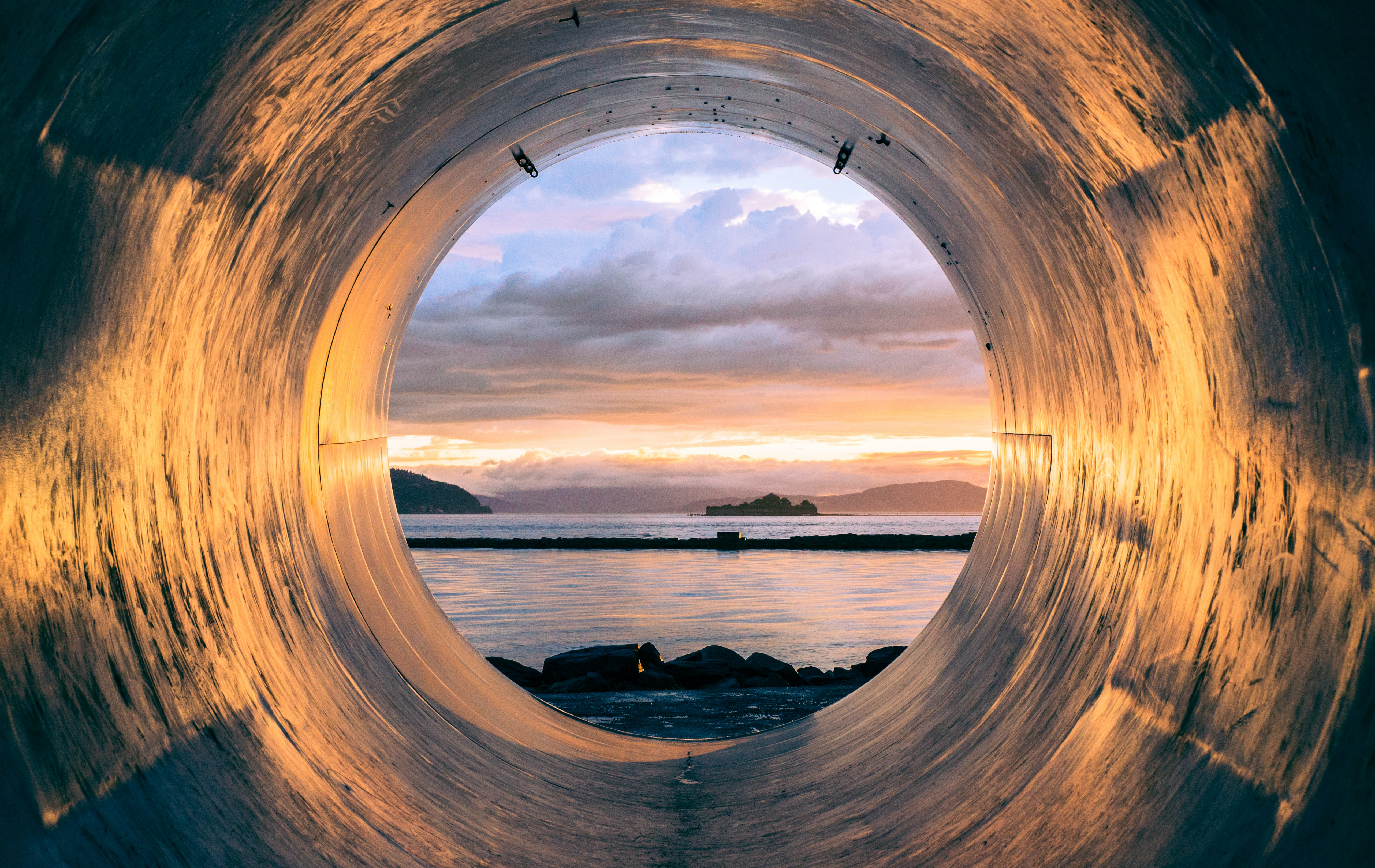 Sunset over the sea seen from the inside of a large pipe