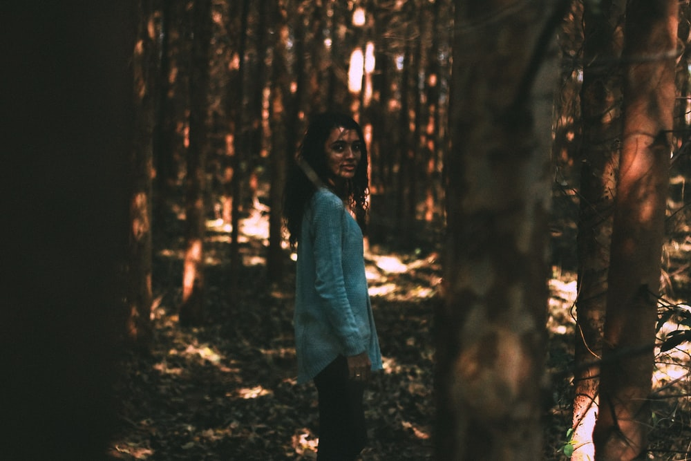 woman in white long sleeve shirt standing in the middle of the woods