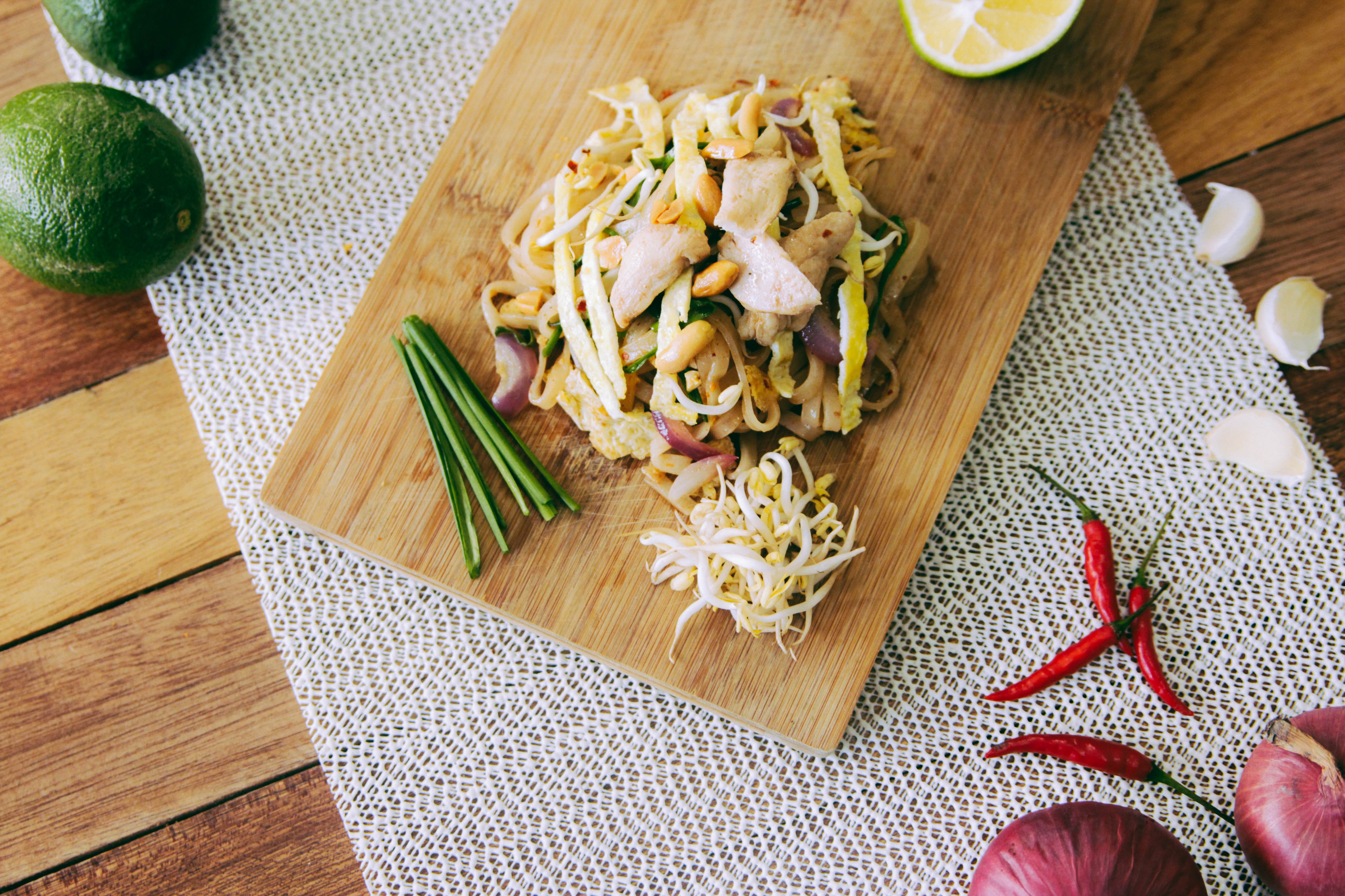 Filipino noodle dish with bean sprouts and vegetables on a cutting board