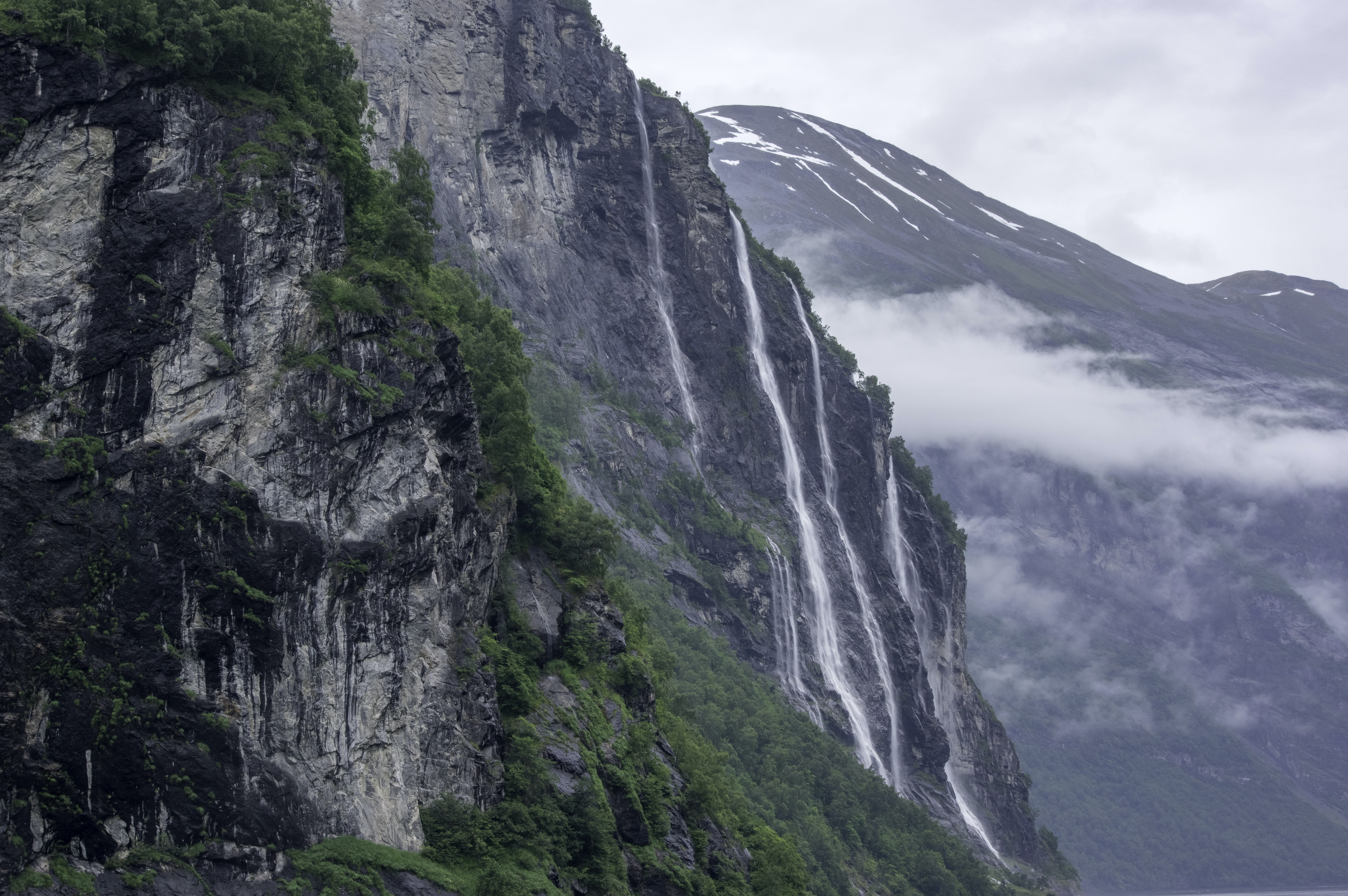 Mountainsides with waterfalls and lush greenery in Geirangerfjord