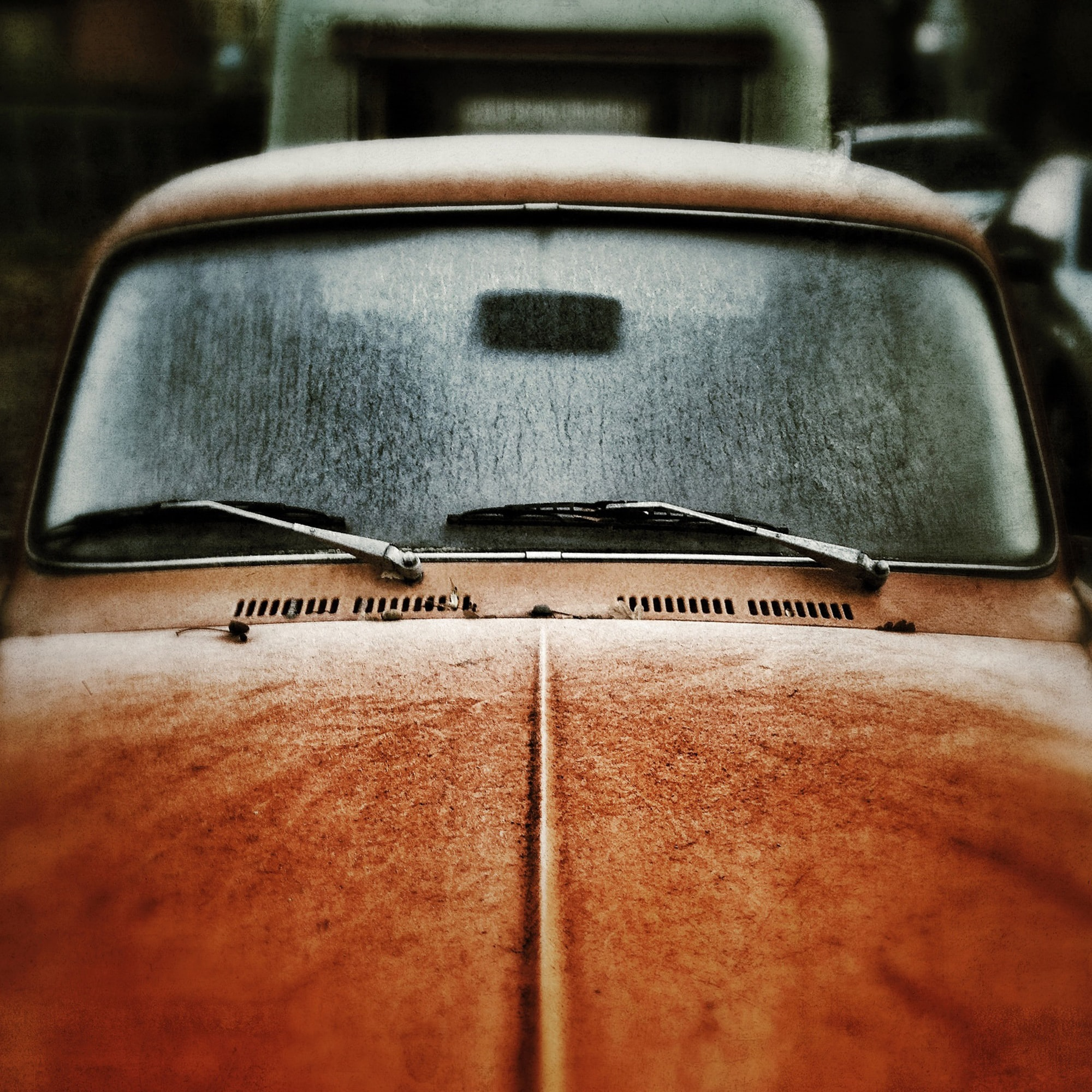 Frost-covered hood and windshield of an orange Volkswagen Beetle