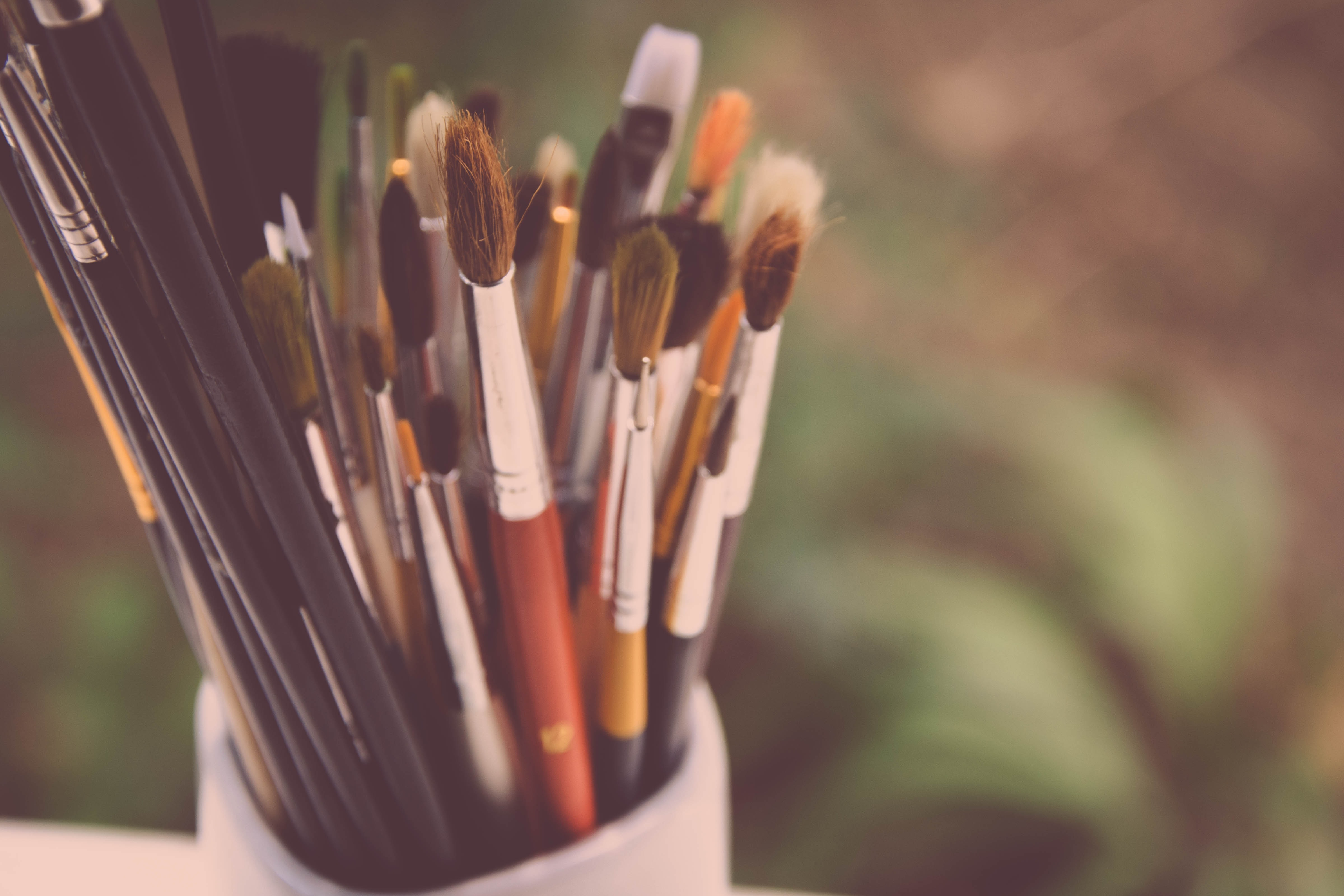 Many paintbrushes in a cup