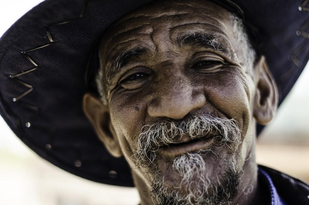 closeup photography of man wearing black hat