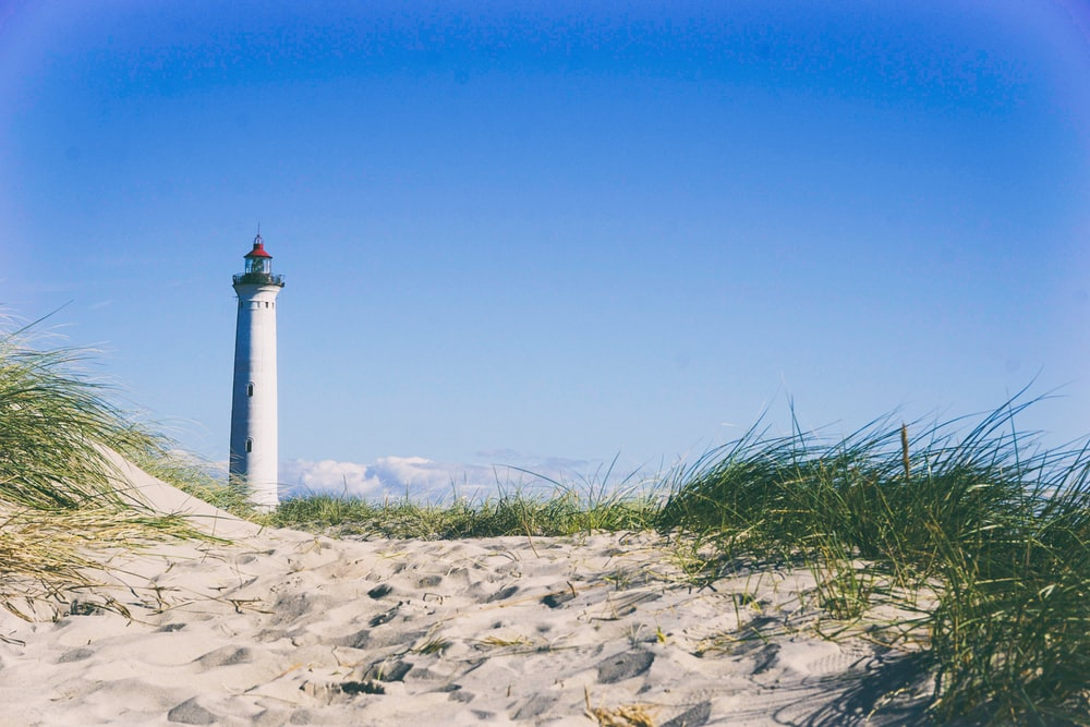 white lighthouse surrounding grass