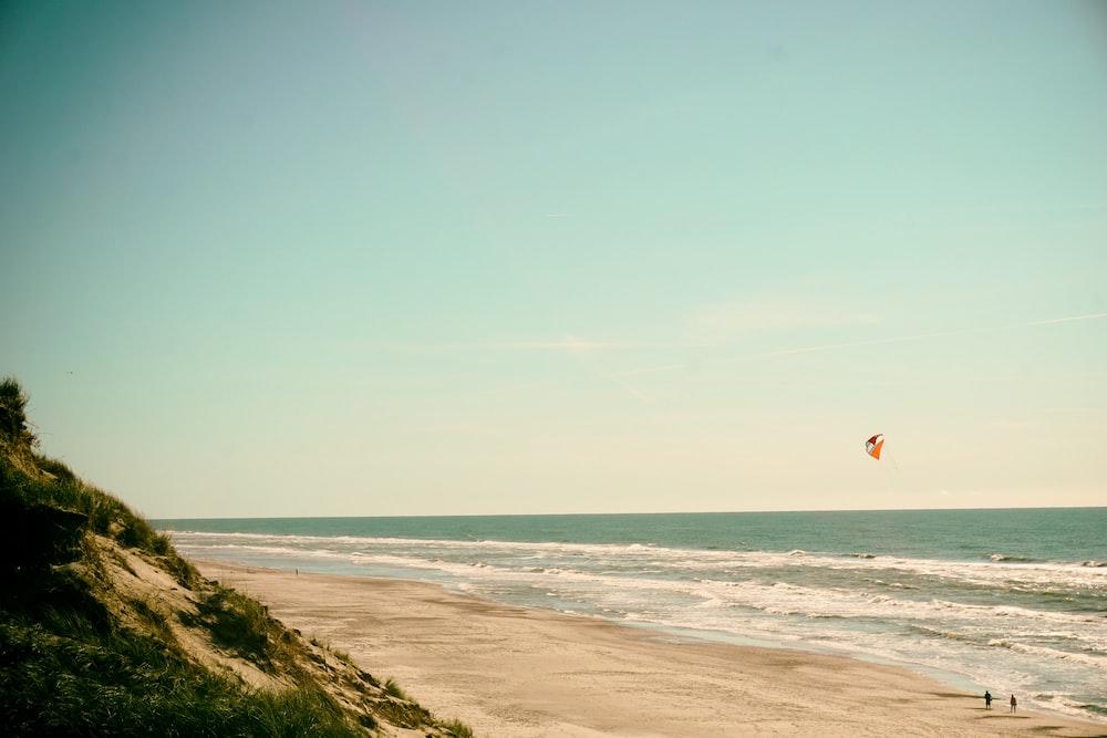 person flying kite on seashore