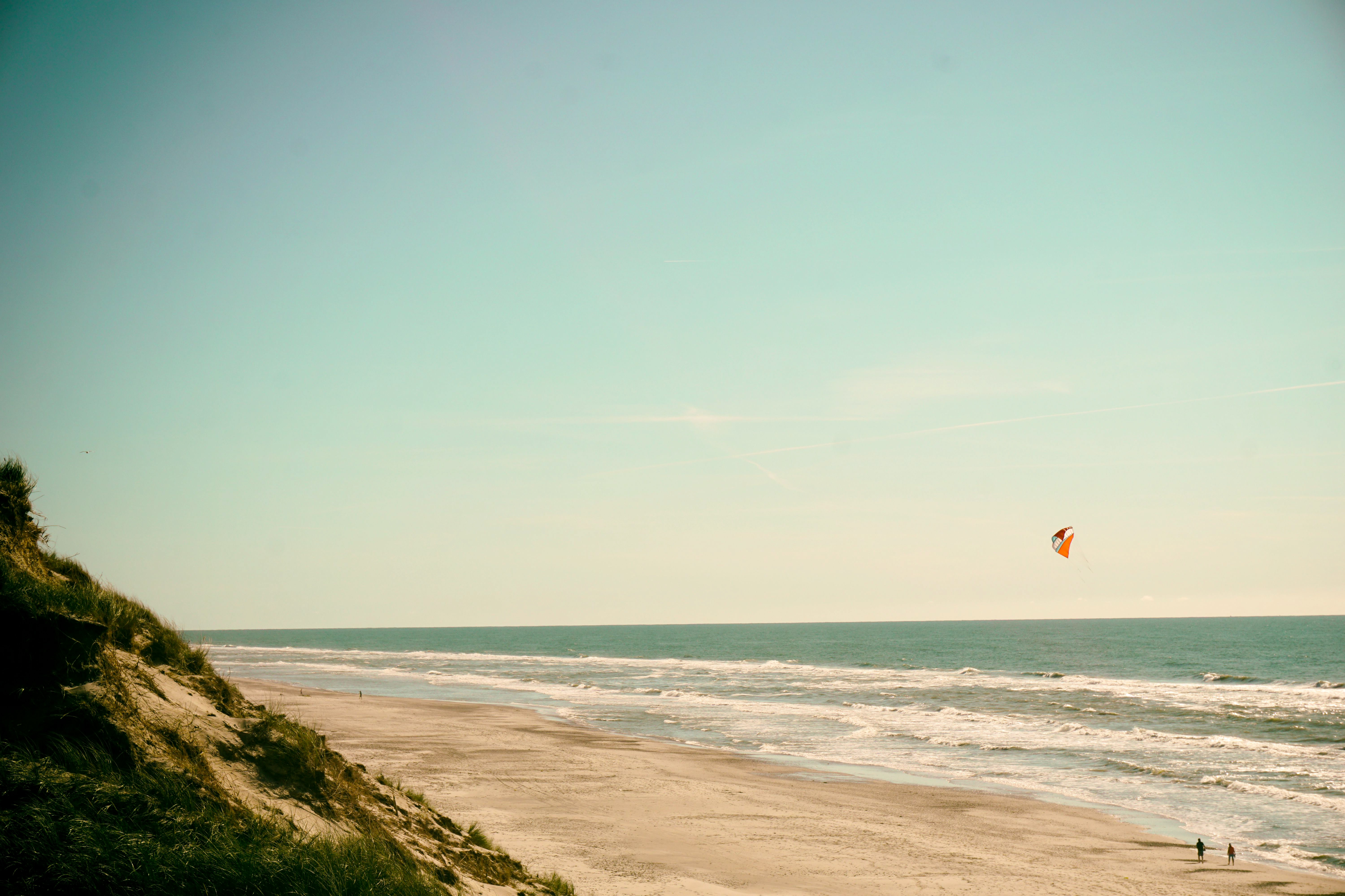 People on the andy ocean coastline with parafoil kite
