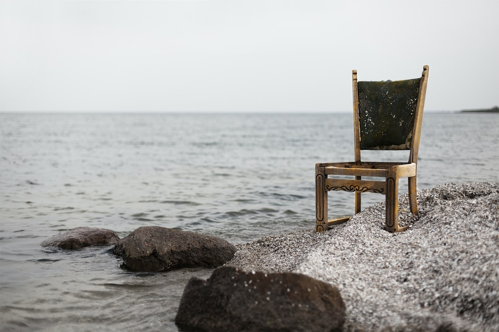 brown wooden parsons chair on gray beach sand