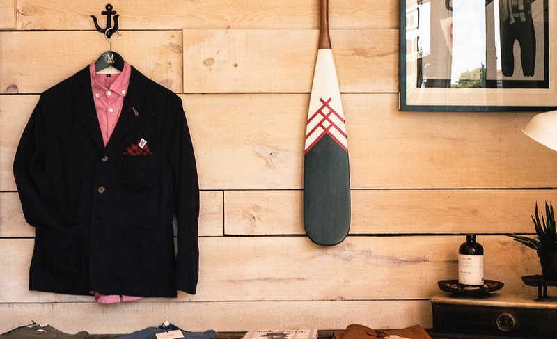black jacket hanging on brown wooden wall beside boat paddle