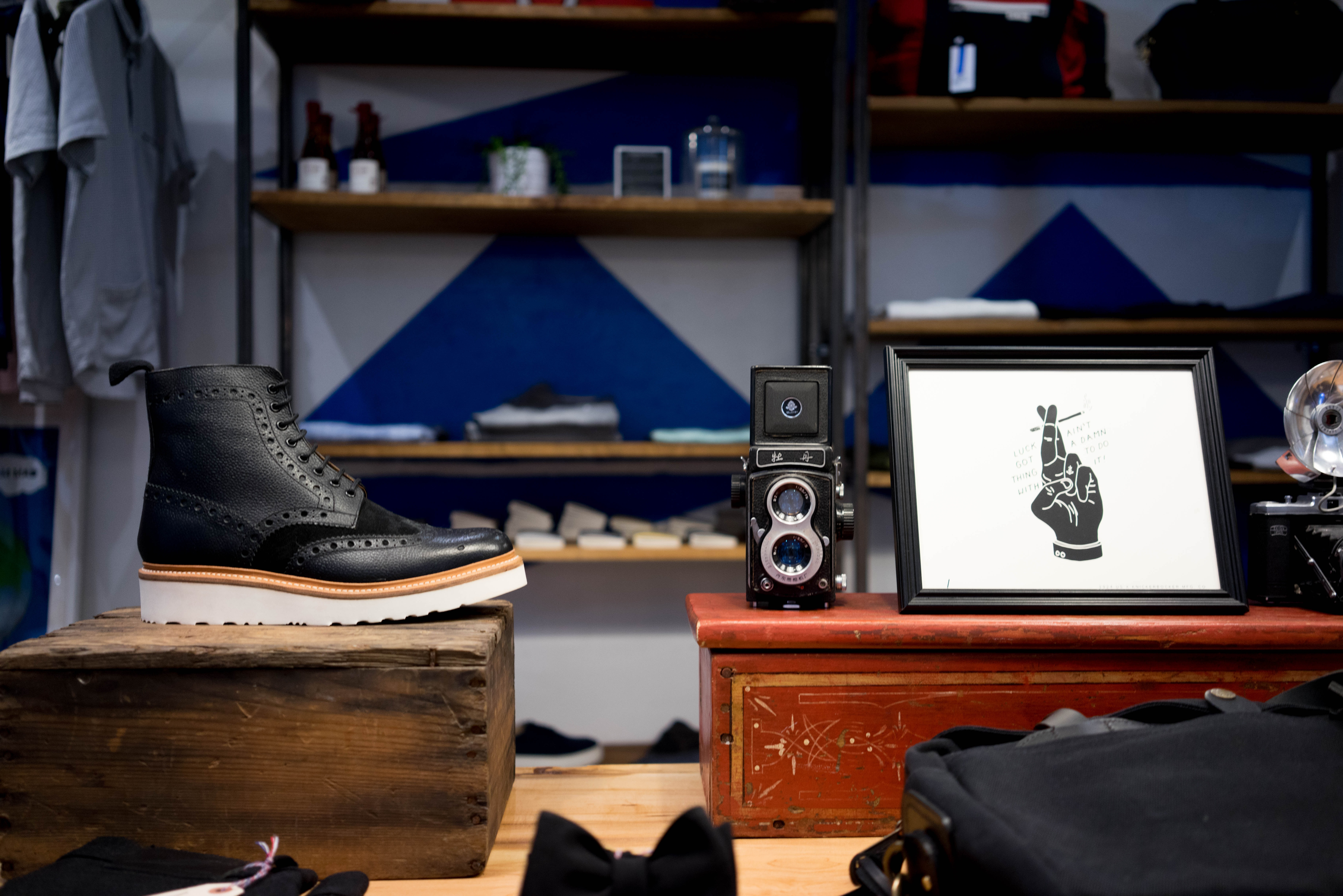 The vintage interior of an apparel store with a poster and a black leather shoe