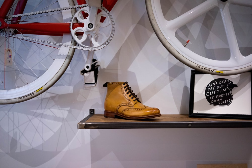 unpaired brown leather wingtip shoe on floating shelf