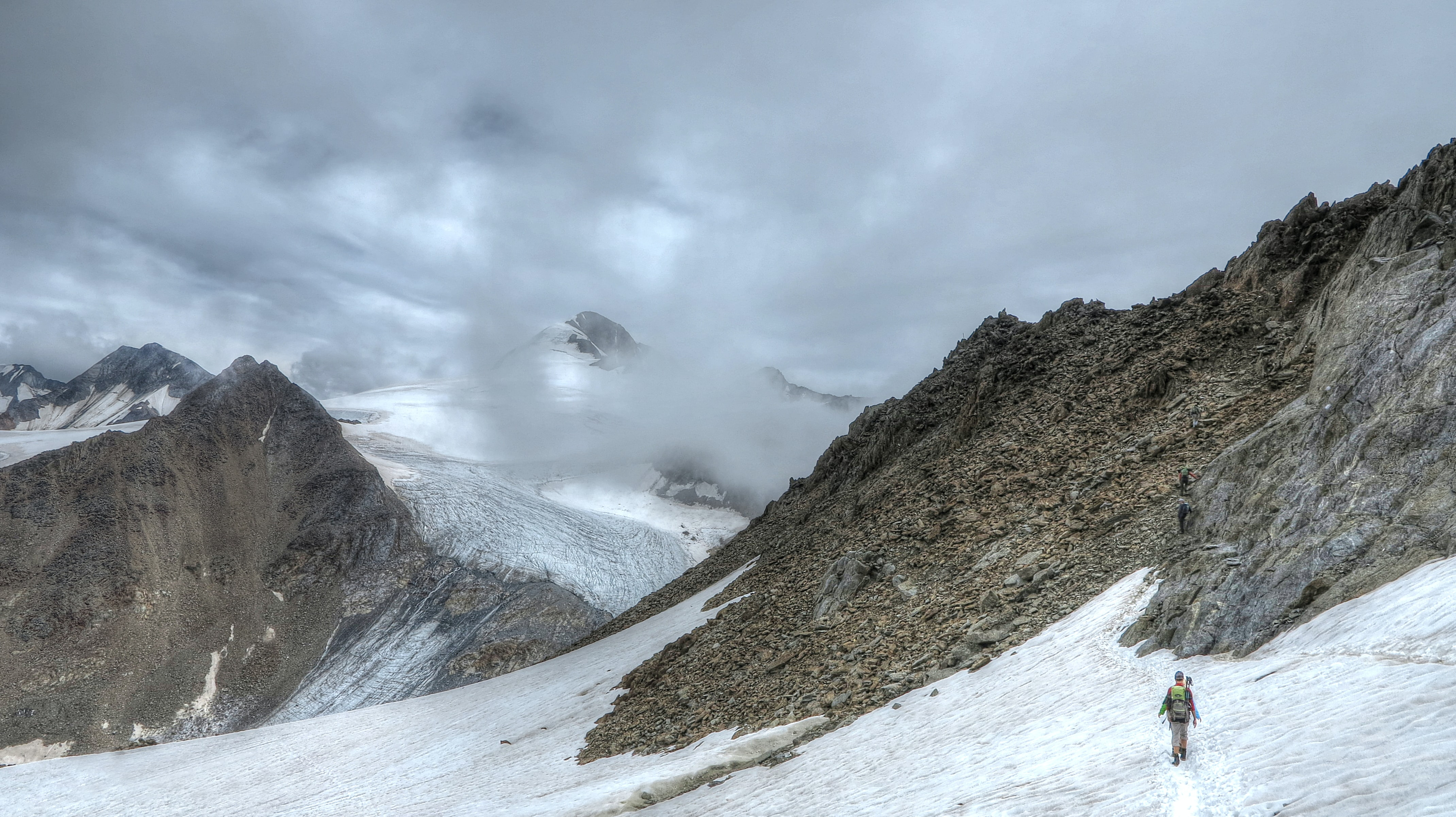 A hiker walking on snow covered mountains with a dark cloudy sky in Similaun.