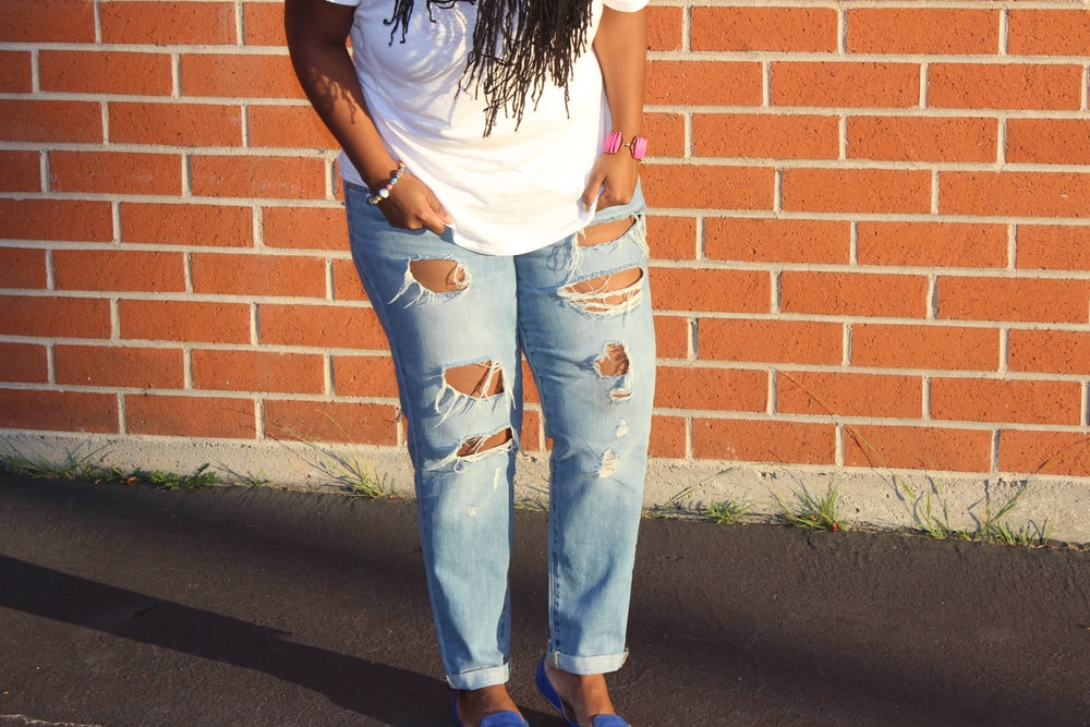 person in blue denim distressed pants