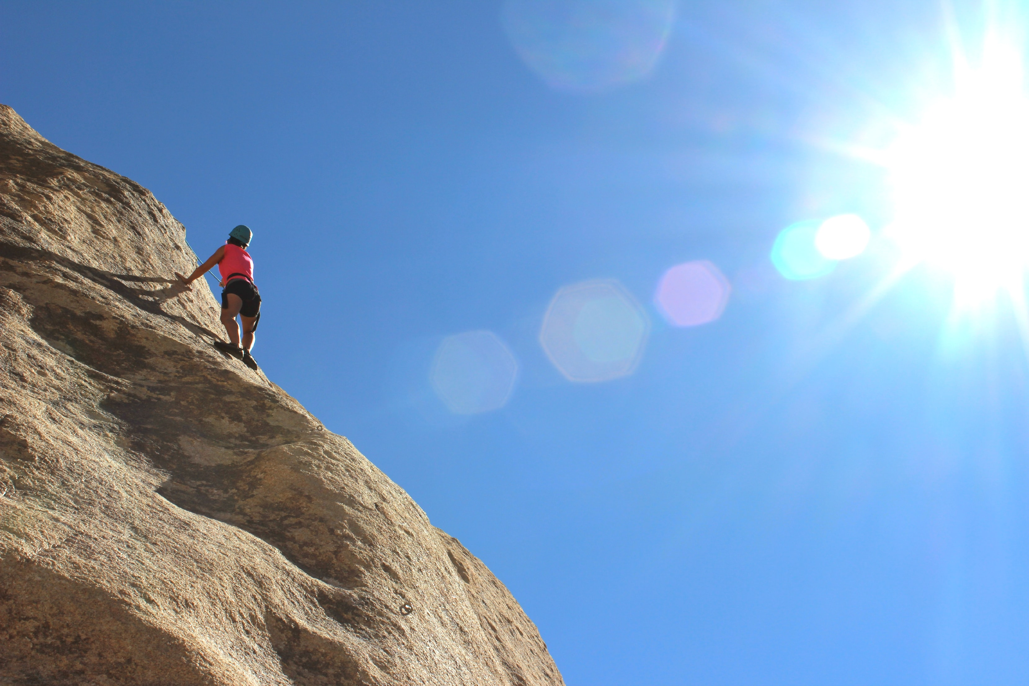 person rock climbing during day time
