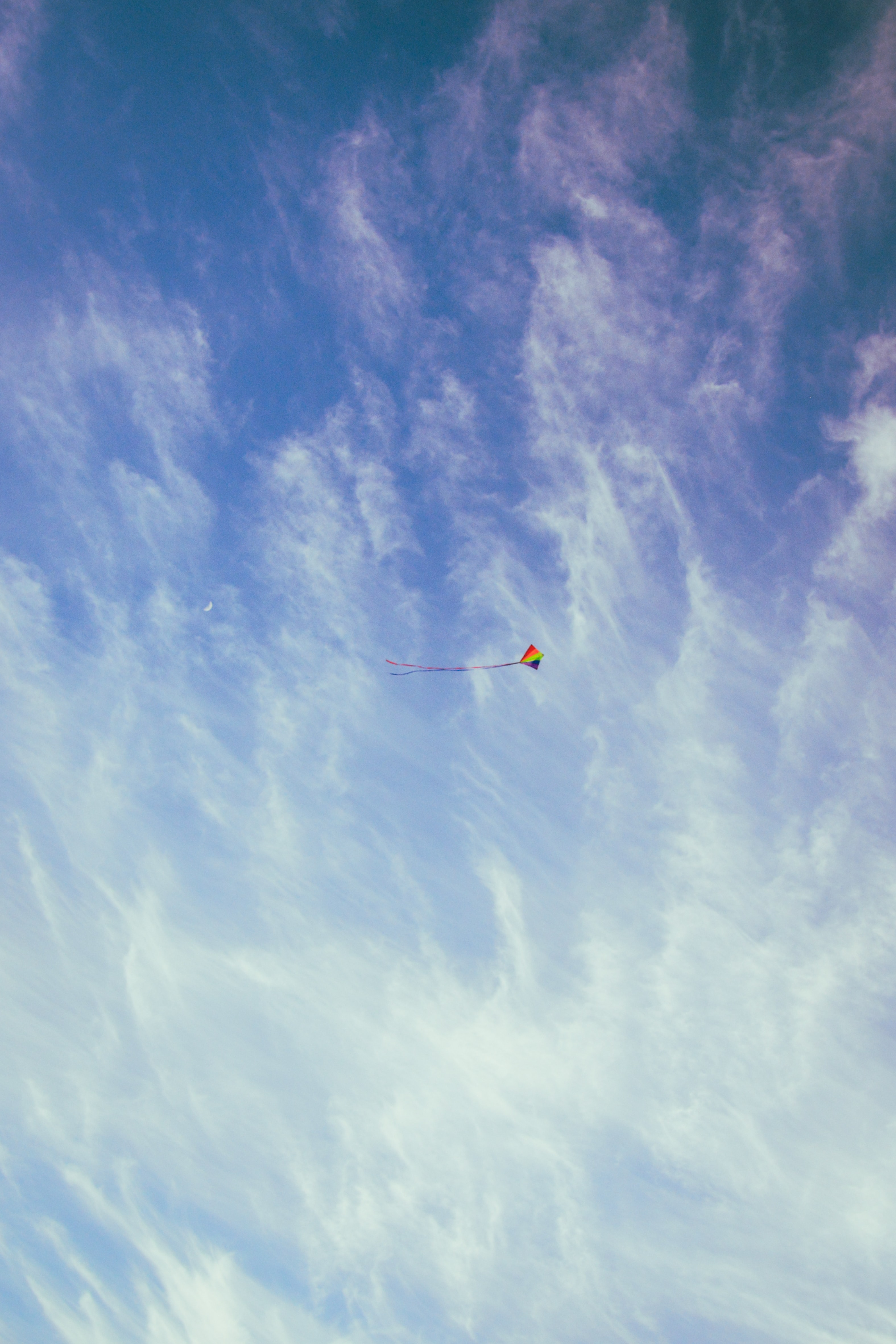 Colorful kite with tail in the sky with wispy clouds and the moon over Oxwich