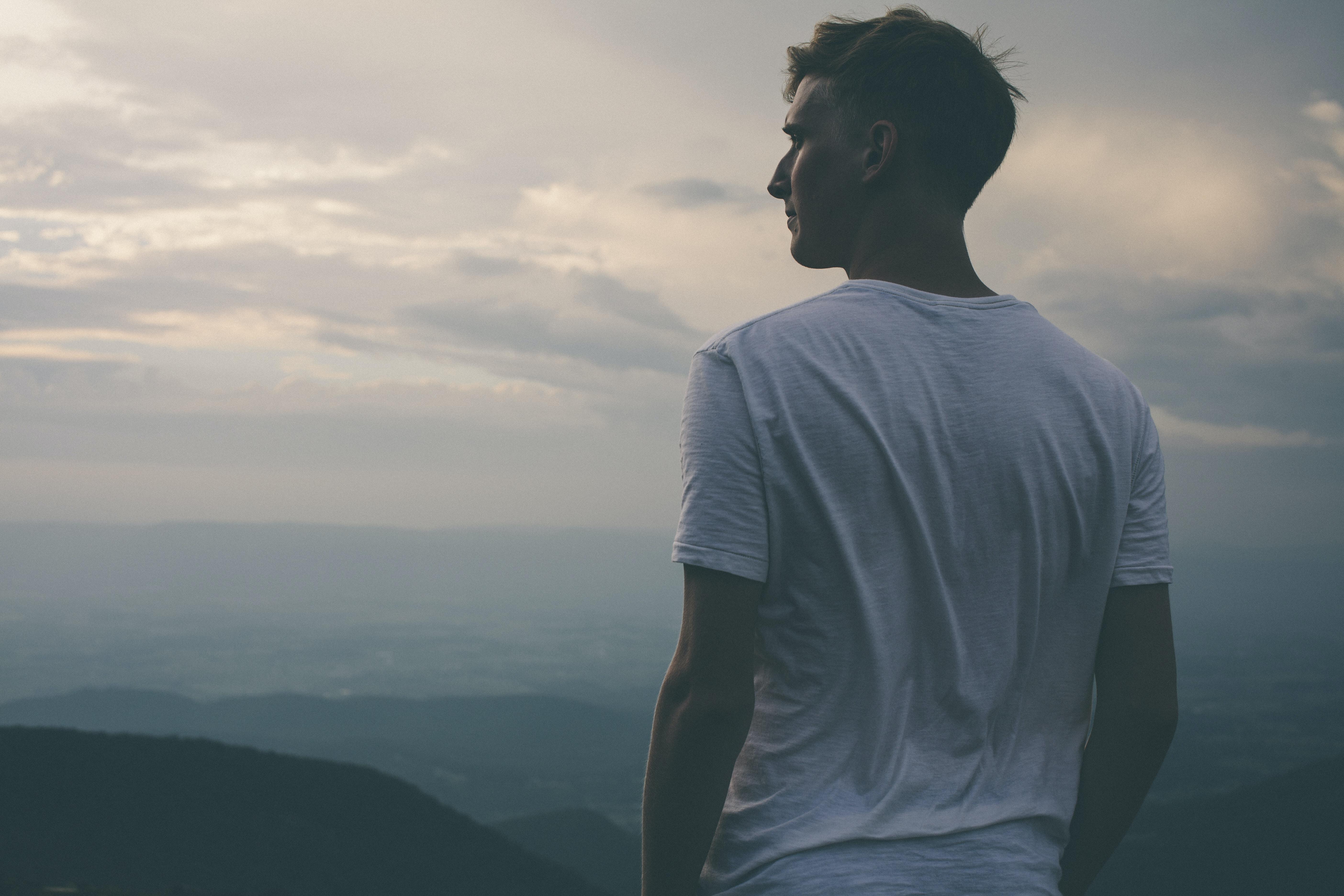 man standing facing mountains during sunset