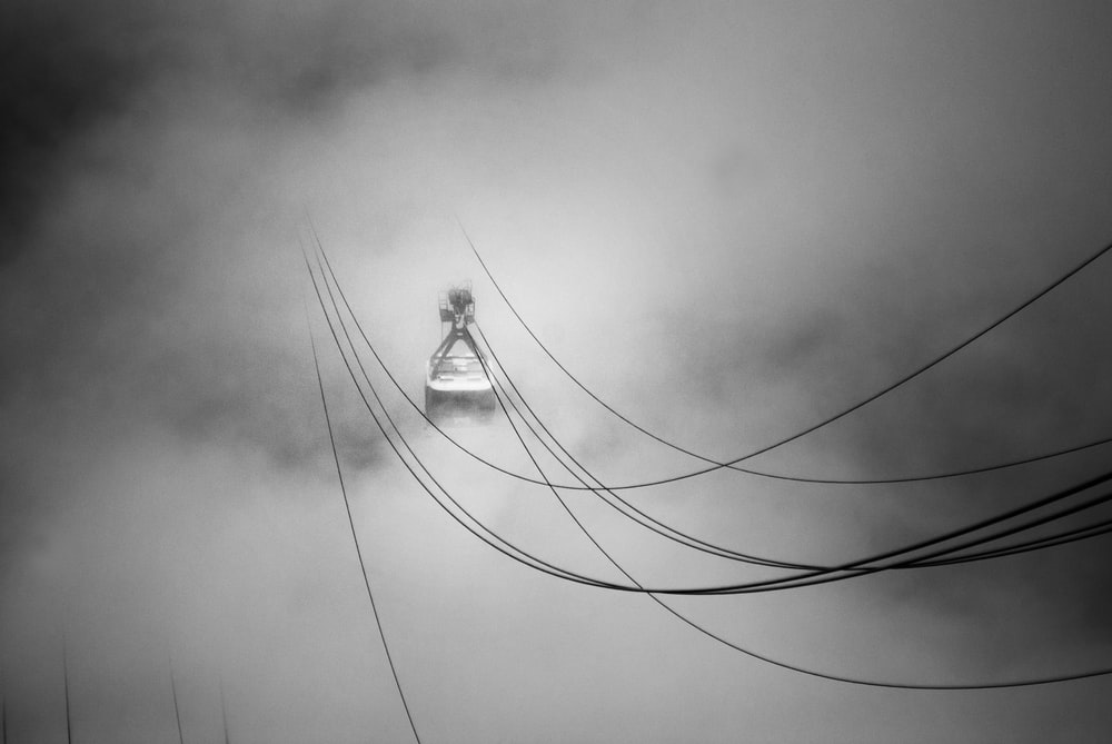 grayscale photo of cable car in the midst of clouds