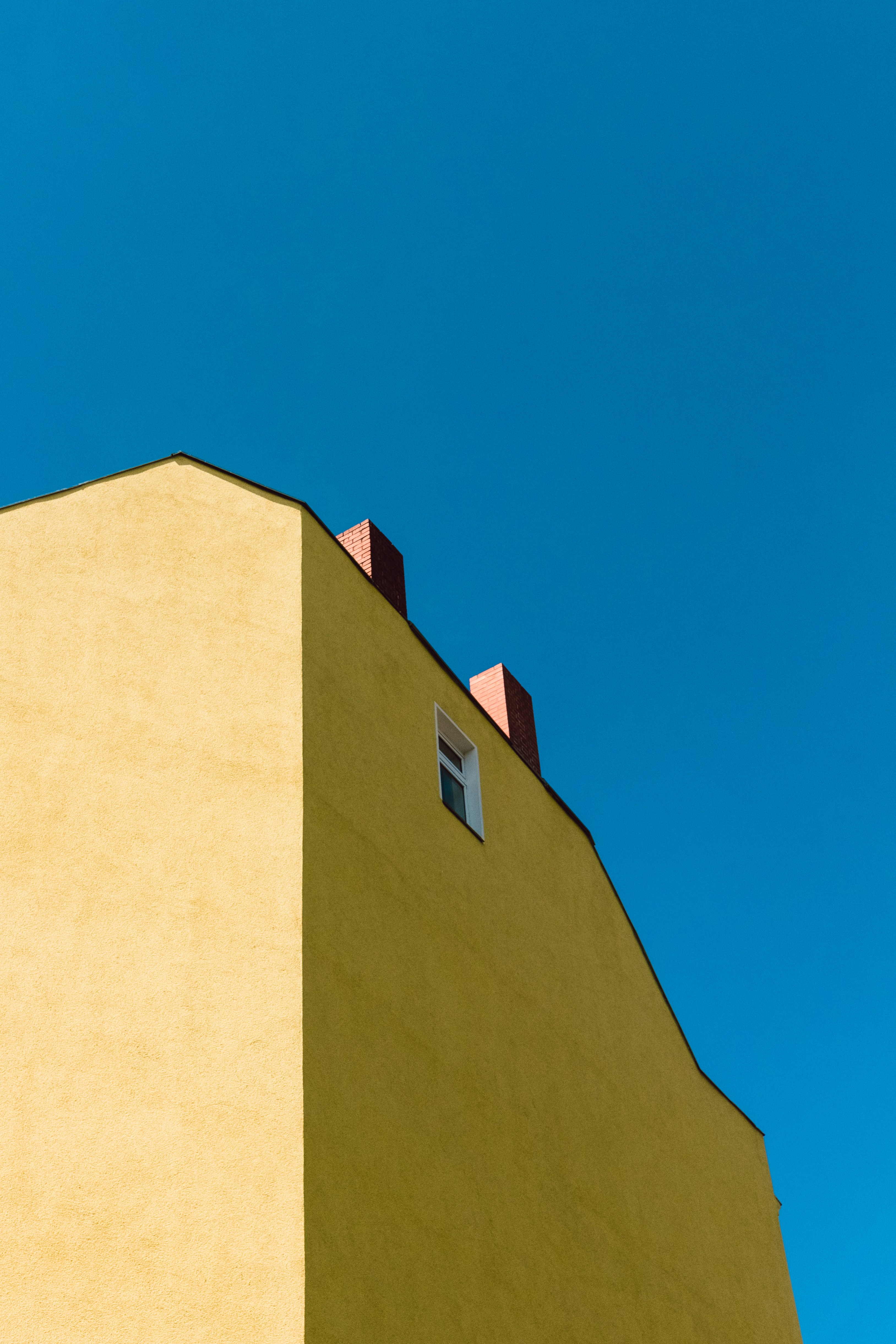 low-angle photography of yellow concrete building under blue sky