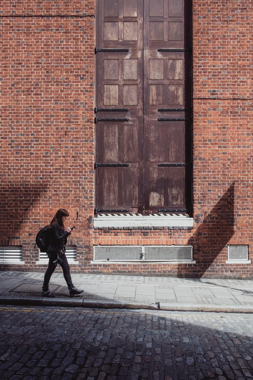 woman walking near brown wooden door during daytime