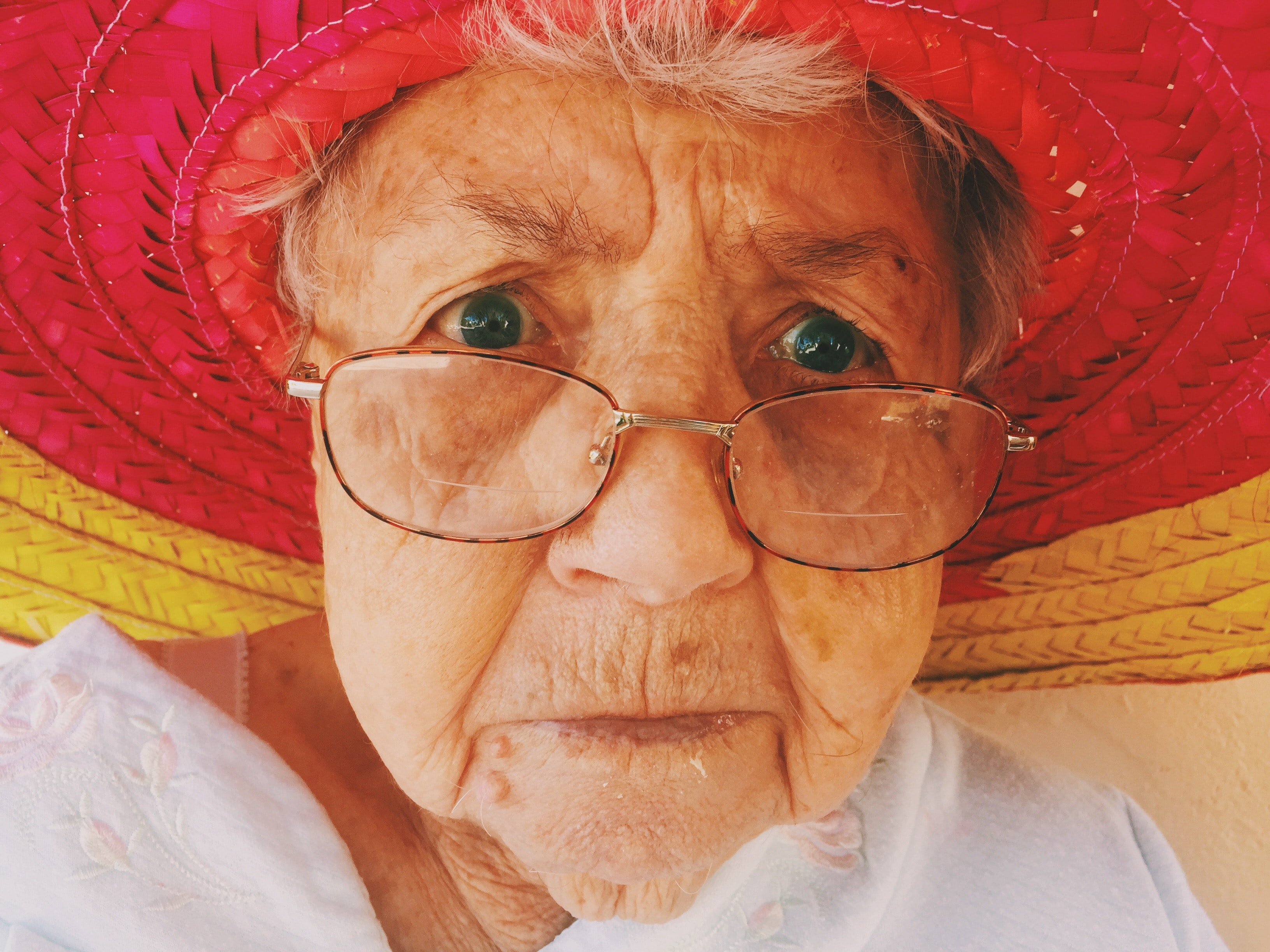 A portrait of an elderly woman in glasses and a red hat