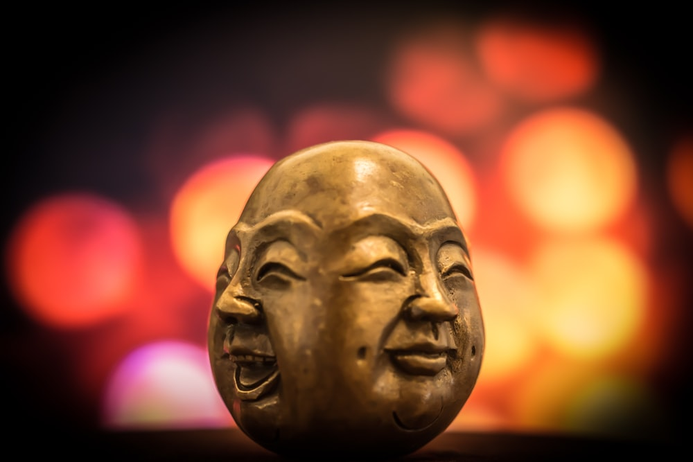 A brass figurine depicting two smiling faces of Buddha, with blurry colored lights in the background