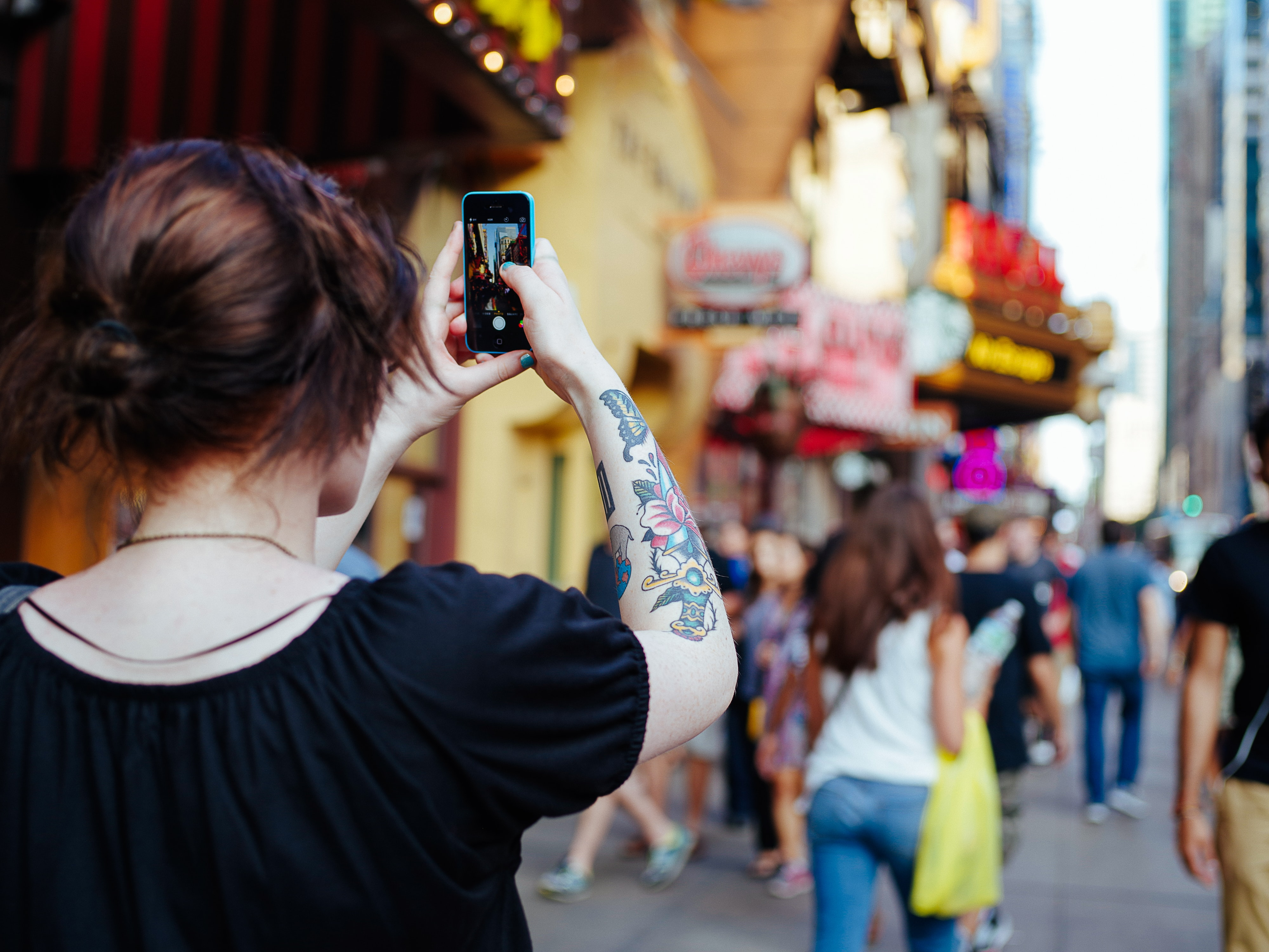 A woman with a tattoo on her arm taking a photo of the Times Square