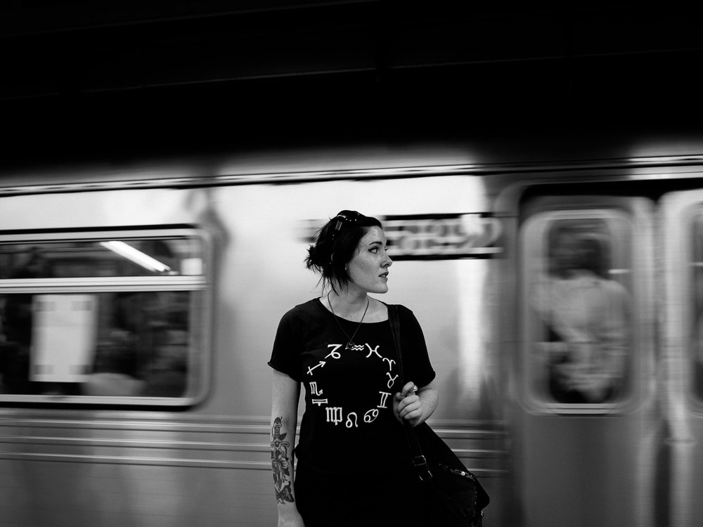 grayscale photography of woman standing near train