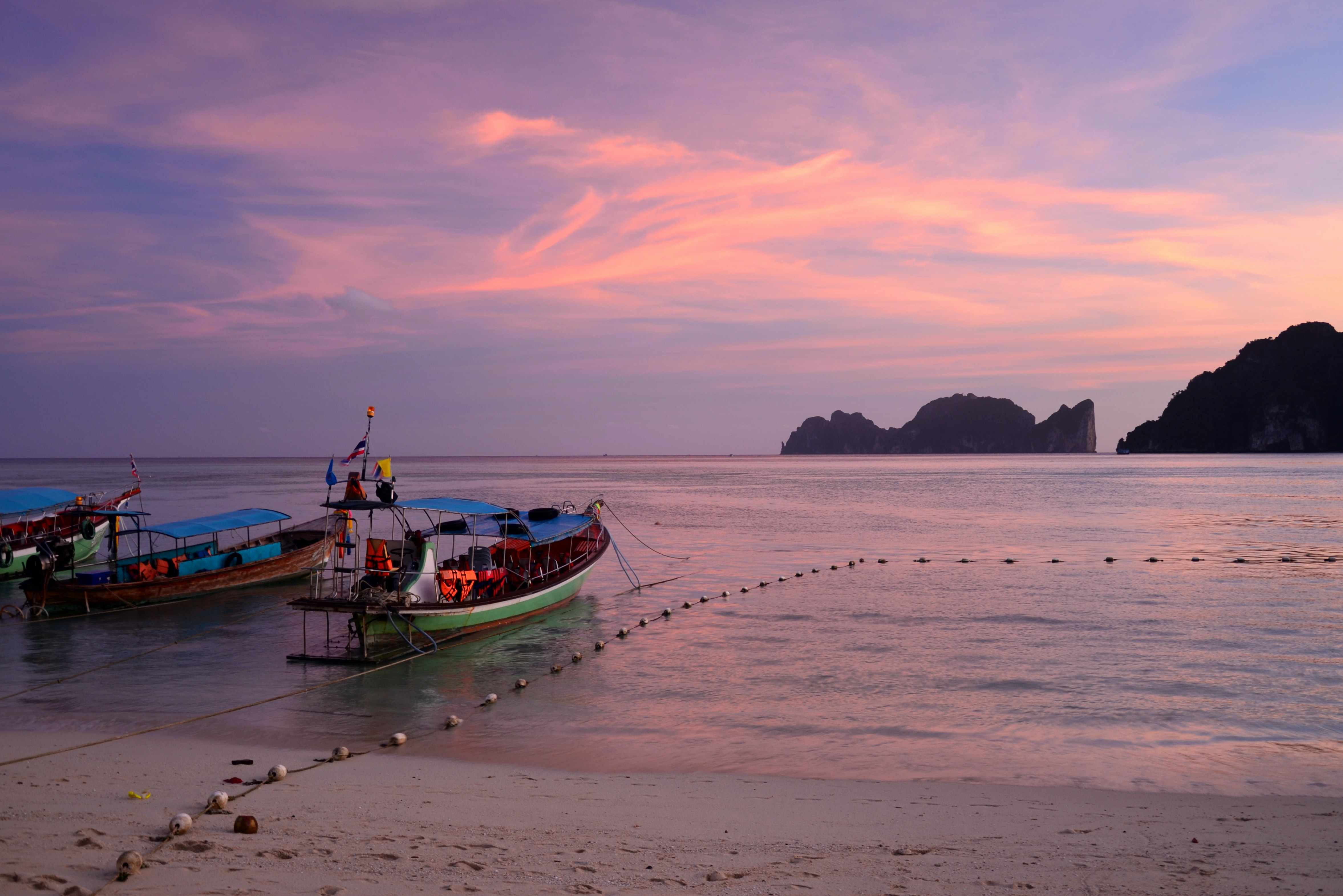Moored fishing boats by the beach in Ko Phi Phi Don at sunrise