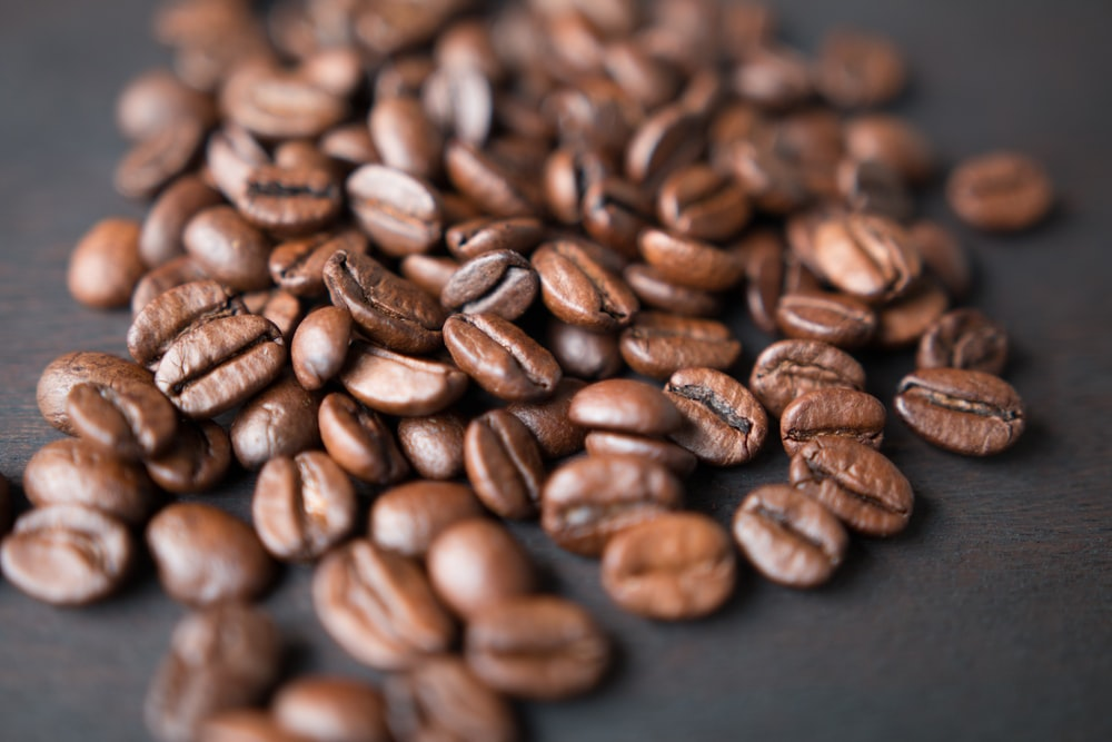brown coffee beans on gray surface