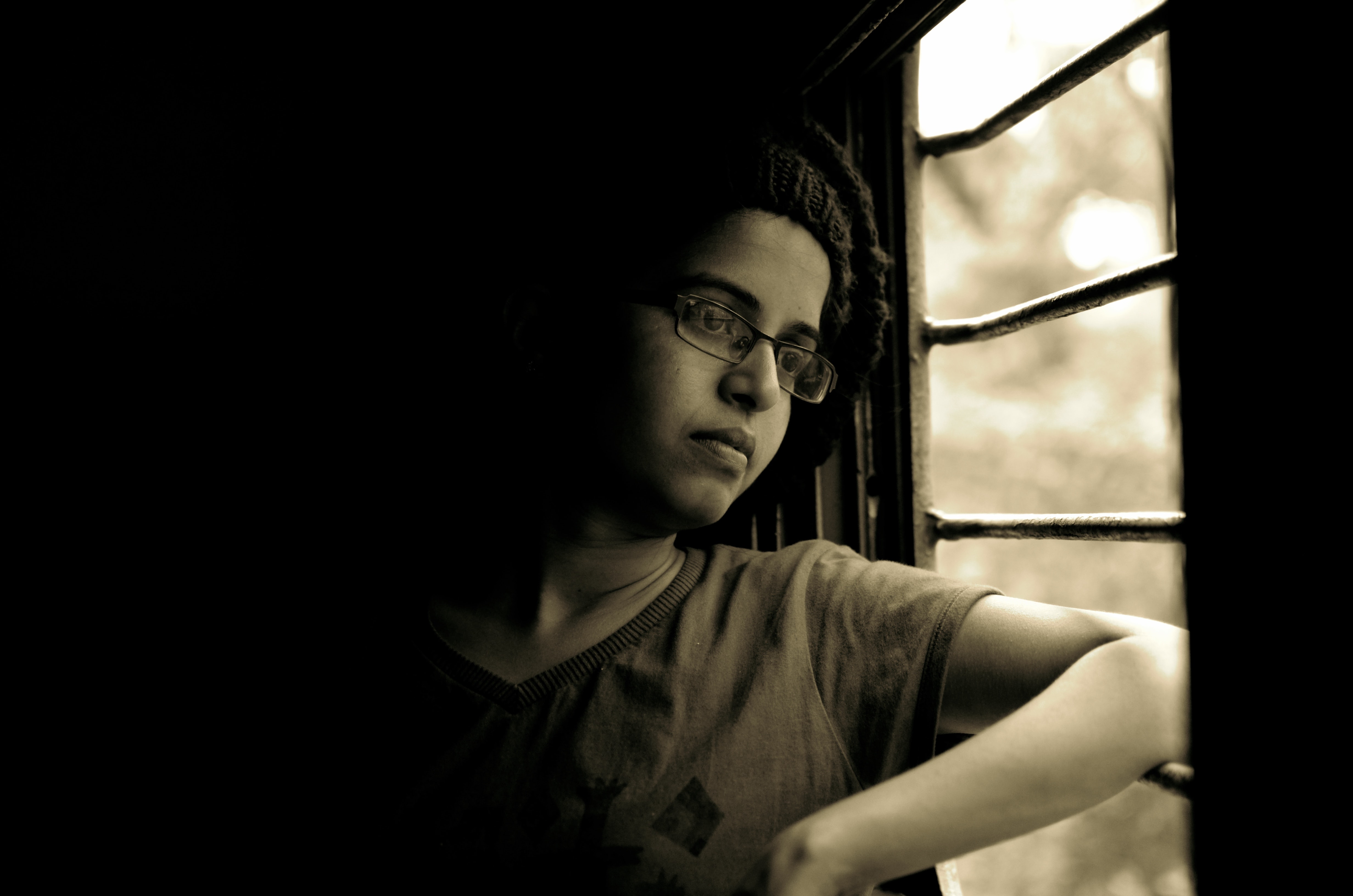 A black-and-white shot of a woman next to a train window in Goa
