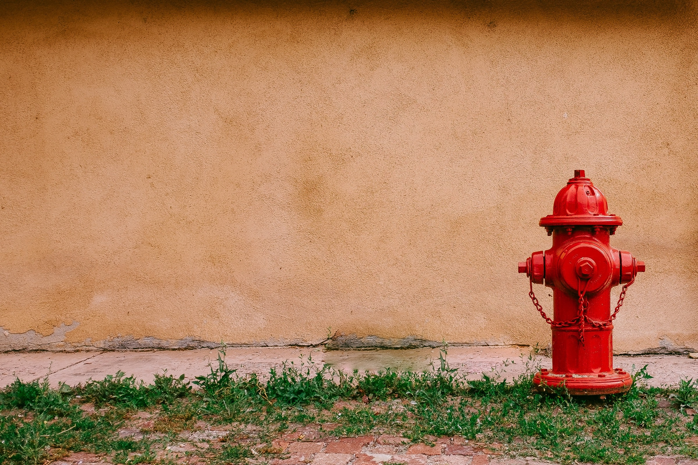 A red fire hydrant next to a wall in Santa Fe