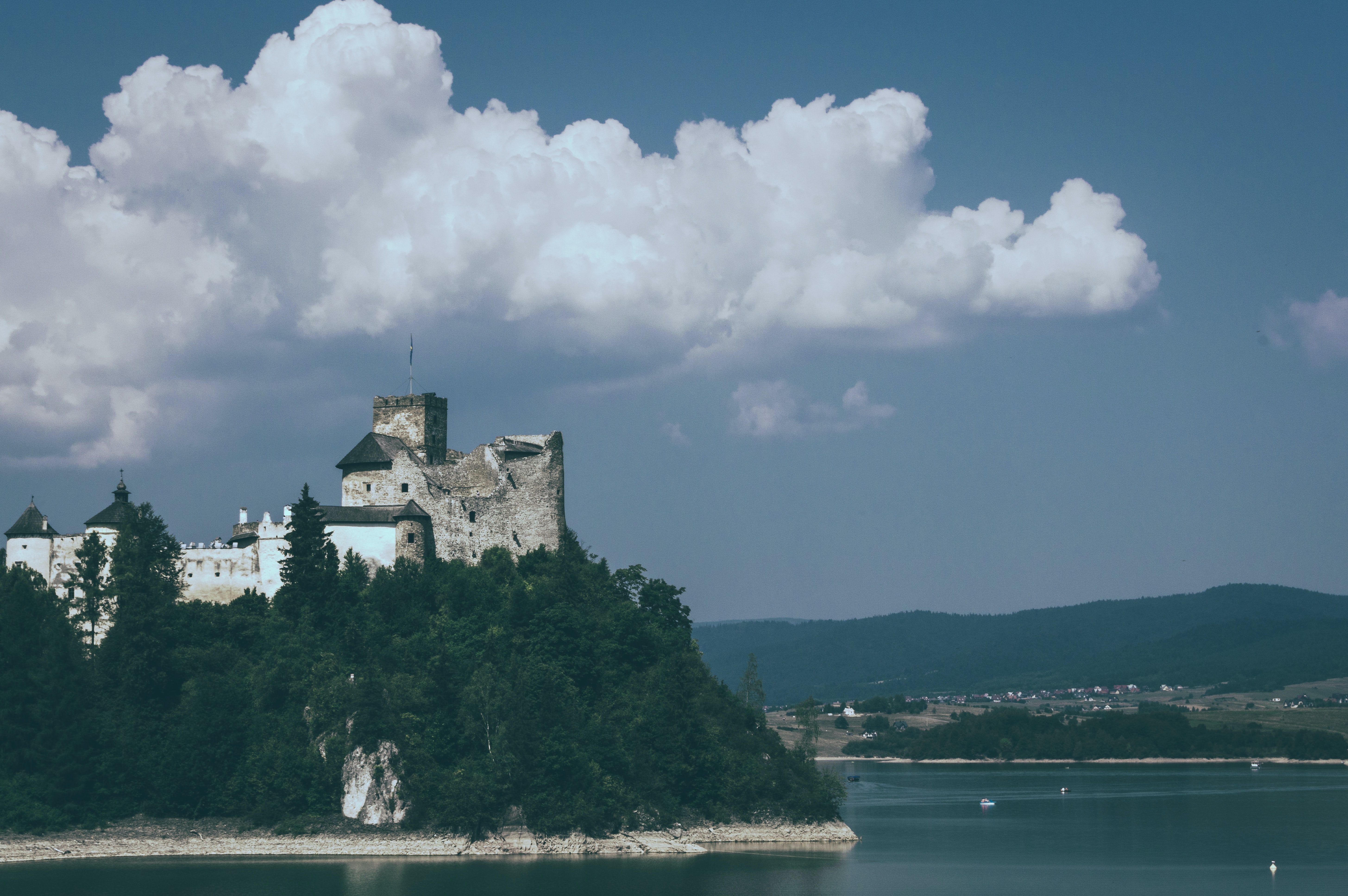 A medieval castle on a hill at the shore of a lake
