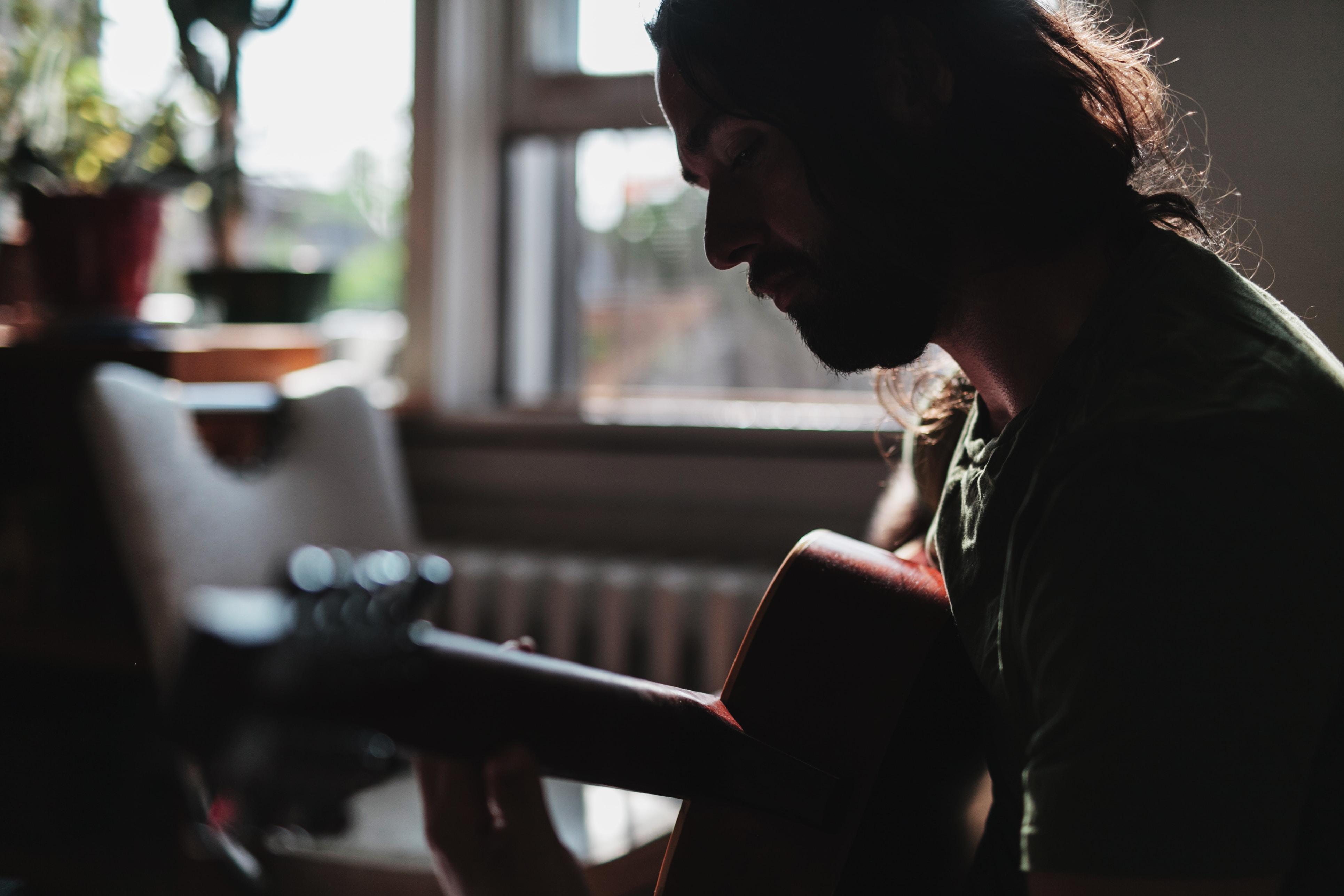 closeup photo of a man playing guitar